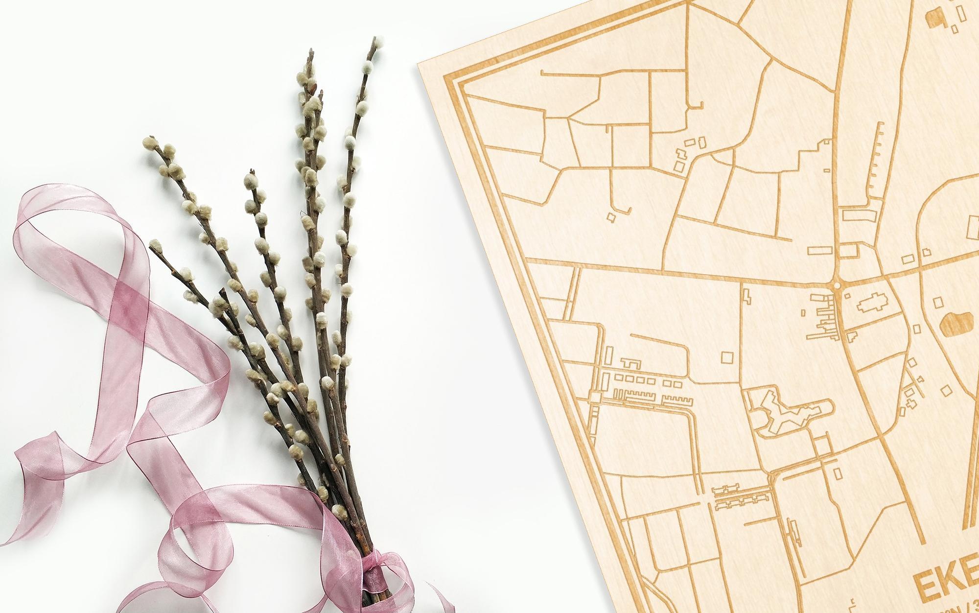Hier ligt de houten plattegrond Eke naast een bloemetje als gepersonaliseerd cadeau voor haar.