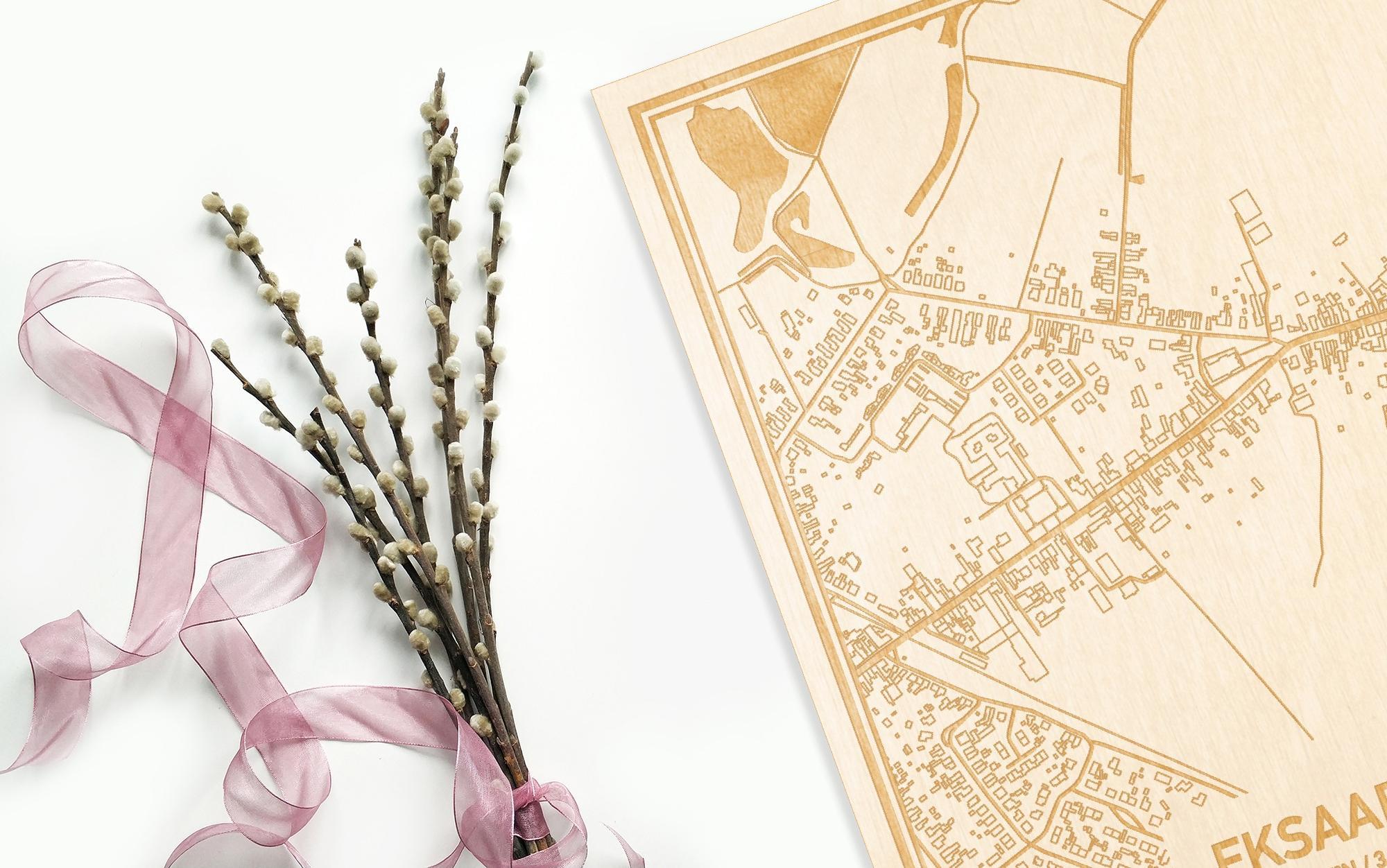 Hier ligt de houten plattegrond Eksaarde naast een bloemetje als gepersonaliseerd cadeau voor haar.