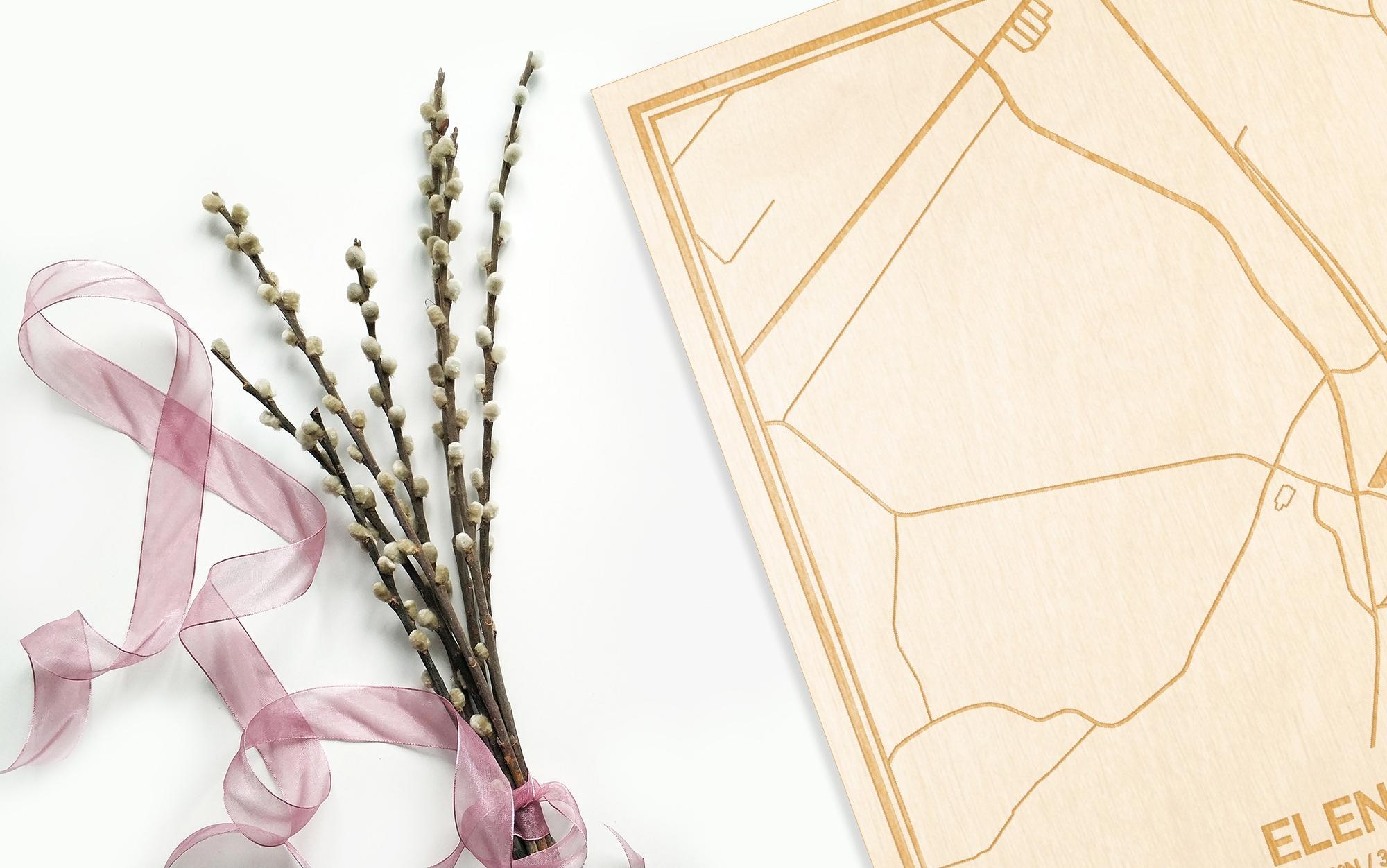 Hier ligt de houten plattegrond Elene naast een bloemetje als gepersonaliseerd cadeau voor haar.