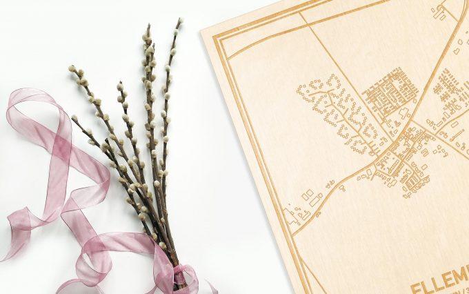 Hier ligt de houten plattegrond Ellemeet naast een bloemetje als gepersonaliseerd cadeau voor haar.