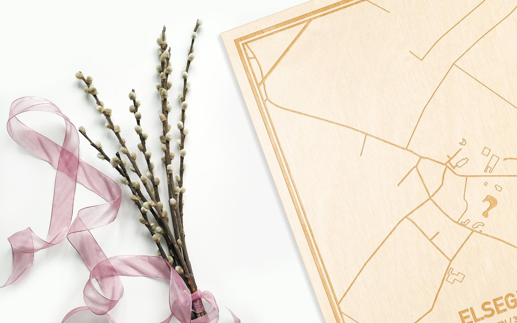 Hier ligt de houten plattegrond Elsegem naast een bloemetje als gepersonaliseerd cadeau voor haar.