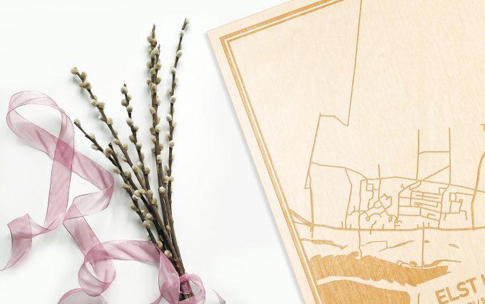 Hier ligt de houten plattegrond Elst Ut naast een bloemetje als gepersonaliseerd cadeau voor haar.