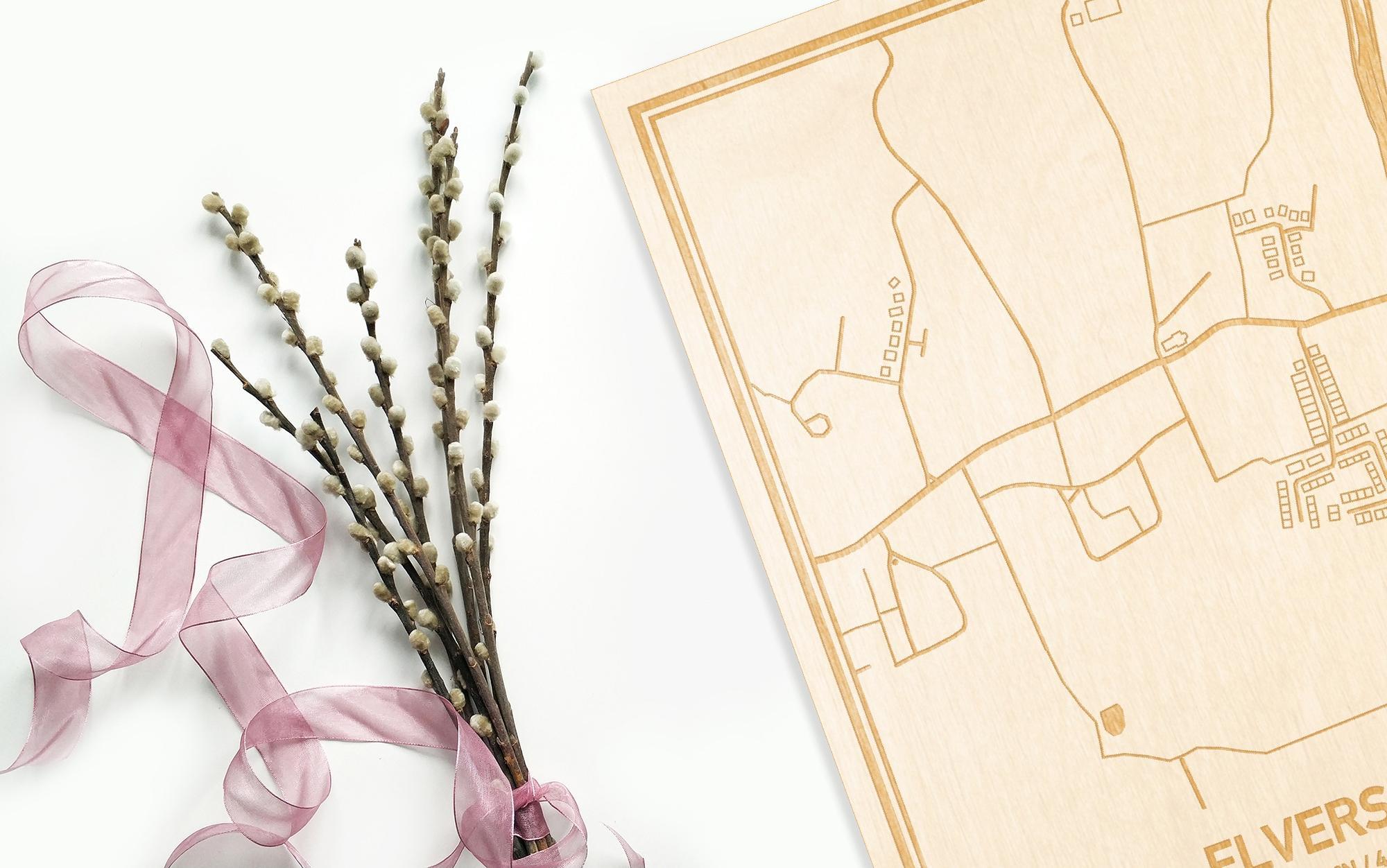 Hier ligt de houten plattegrond Elversele naast een bloemetje als gepersonaliseerd cadeau voor haar.