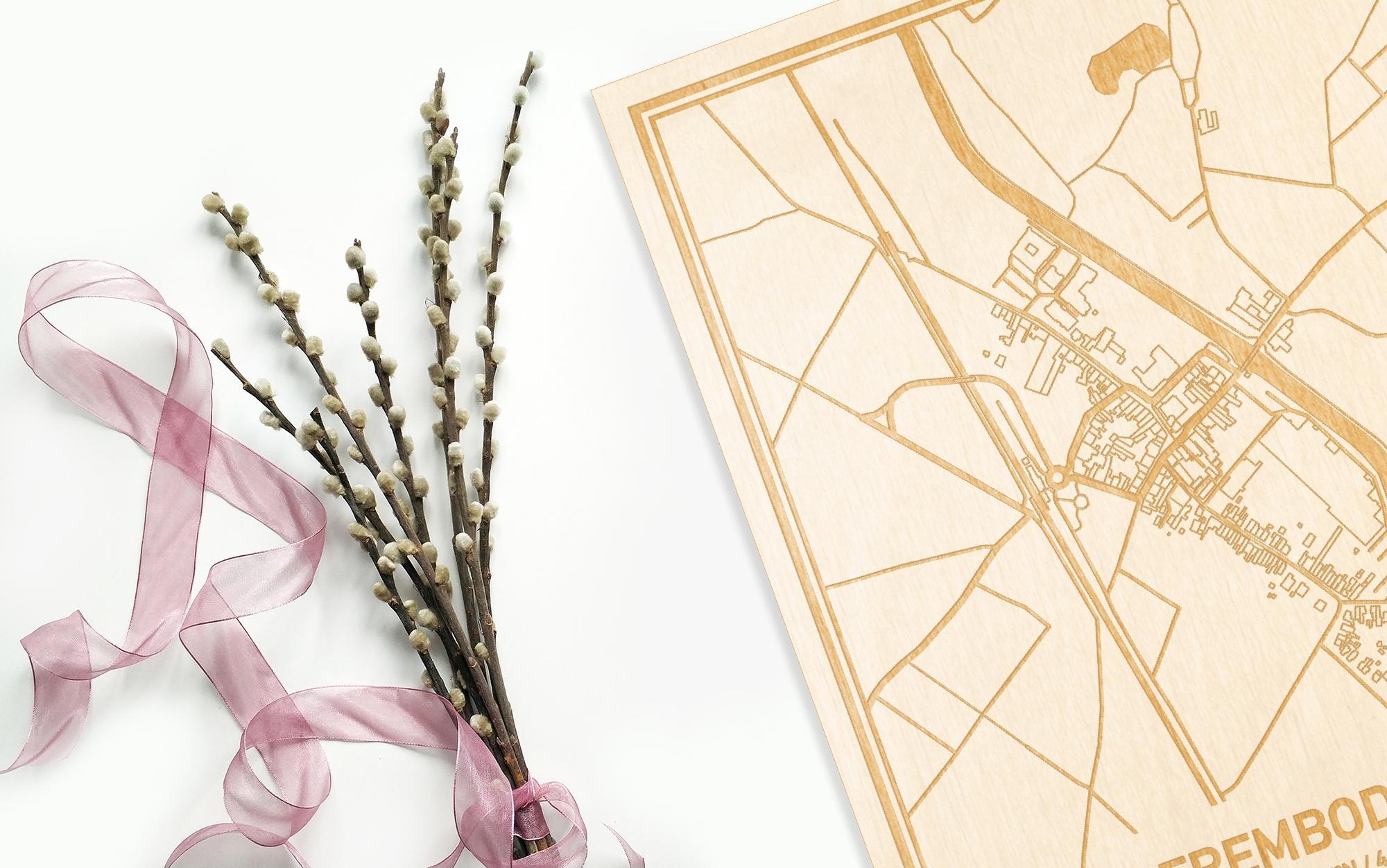 Hier ligt de houten plattegrond Erembodegem naast een bloemetje als gepersonaliseerd cadeau voor haar.