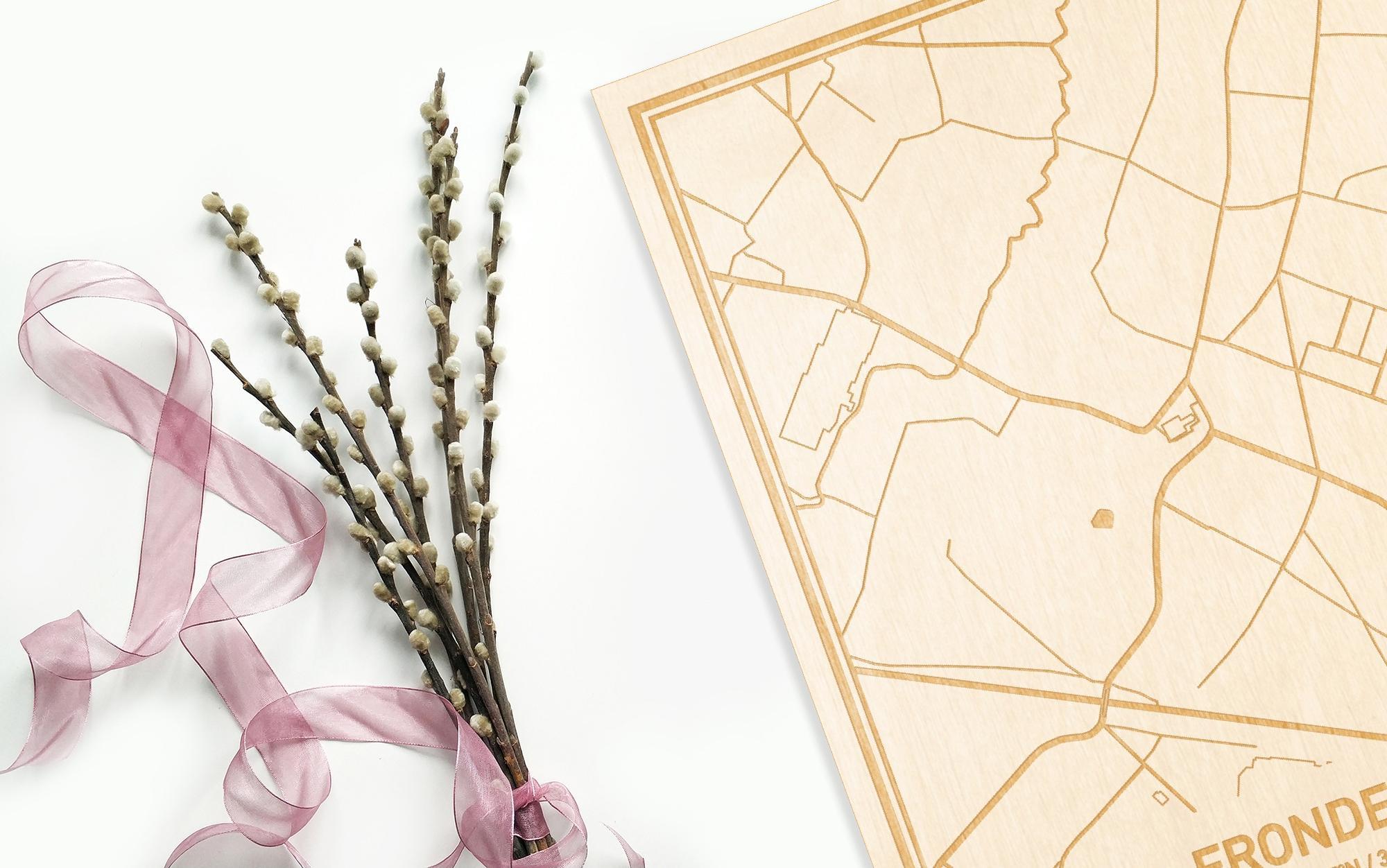 Hier ligt de houten plattegrond Erondegem naast een bloemetje als gepersonaliseerd cadeau voor haar.
