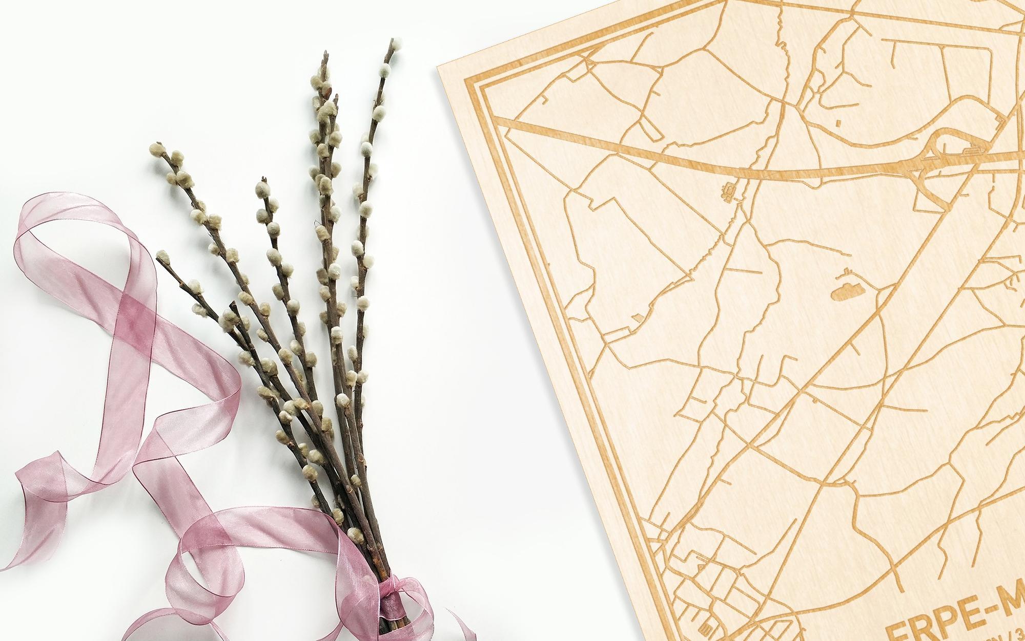 Hier ligt de houten plattegrond Erpe-Mere naast een bloemetje als gepersonaliseerd cadeau voor haar.