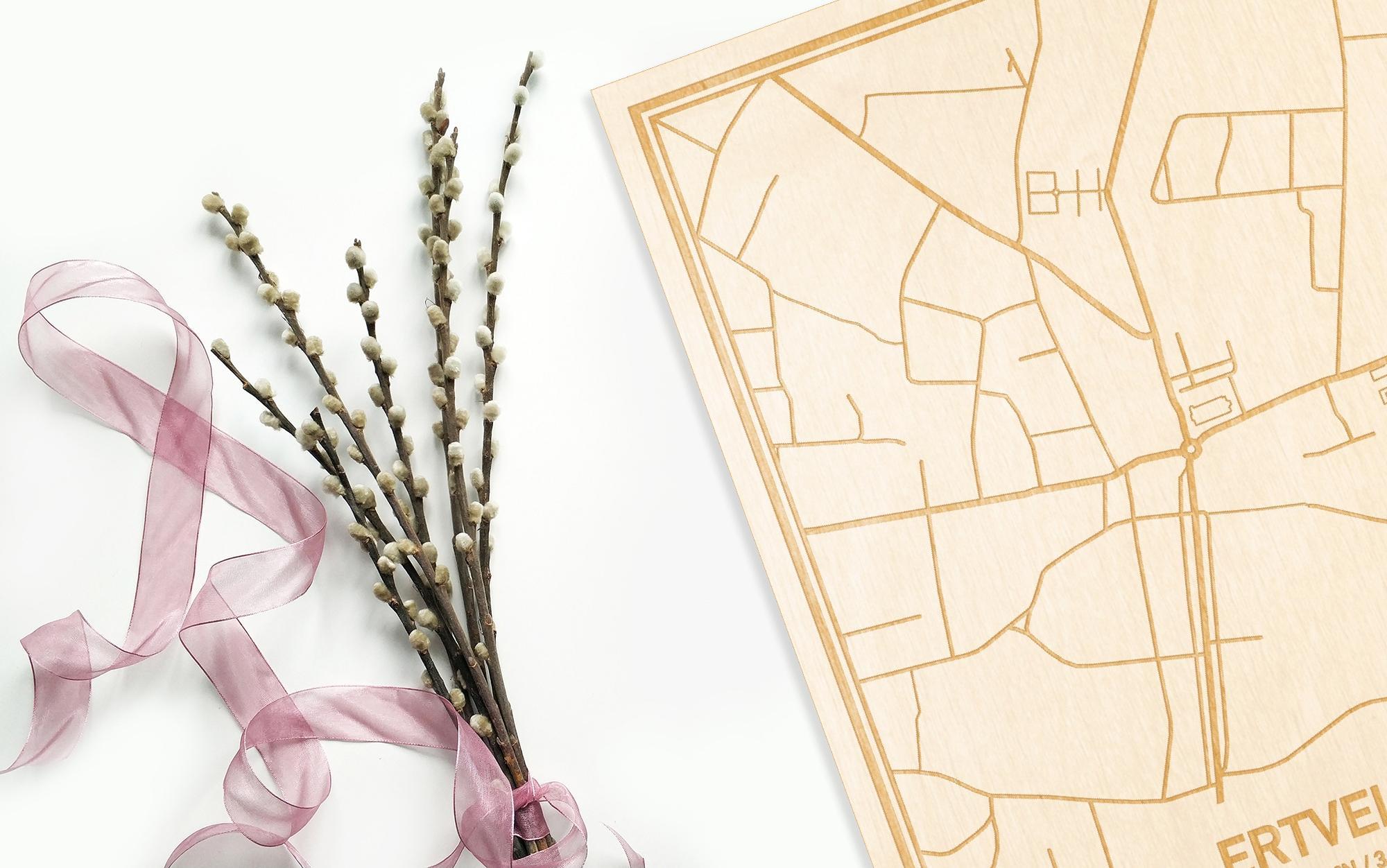 Hier ligt de houten plattegrond Ertvelde naast een bloemetje als gepersonaliseerd cadeau voor haar.