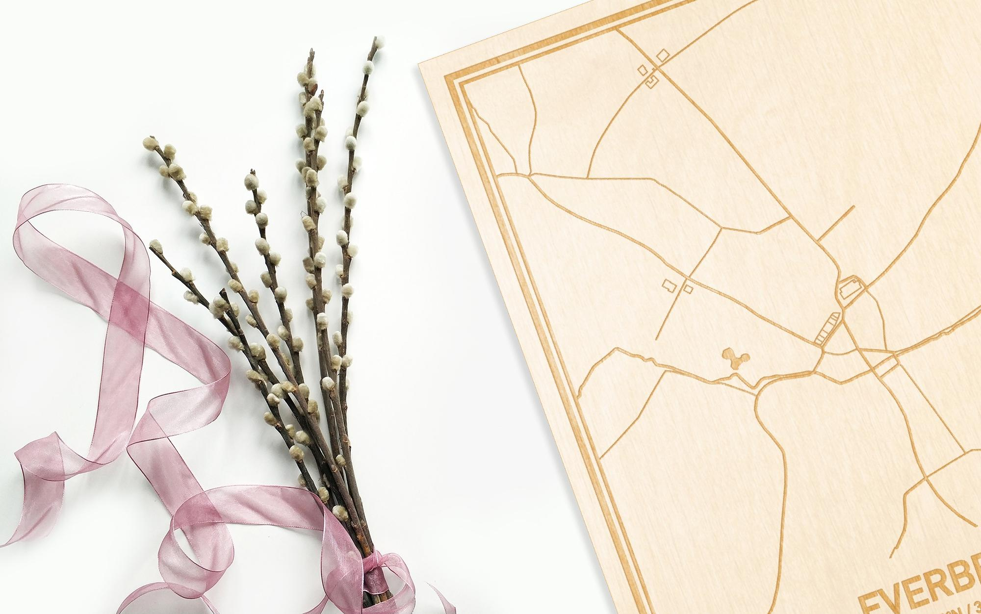 Hier ligt de houten plattegrond Everbeek naast een bloemetje als gepersonaliseerd cadeau voor haar.
