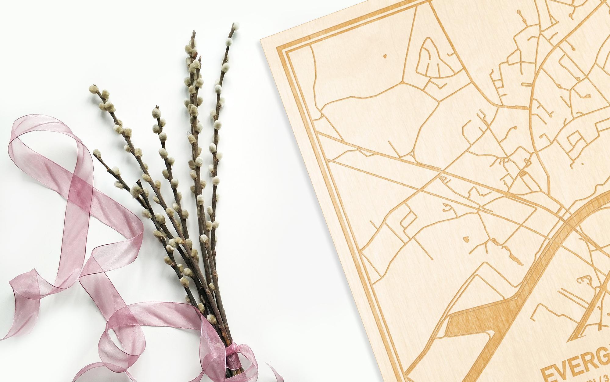 Hier ligt de houten plattegrond Evergem naast een bloemetje als gepersonaliseerd cadeau voor haar.