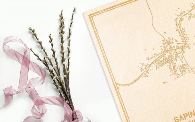 Hier ligt de houten plattegrond Gapinge naast een bloemetje als gepersonaliseerd cadeau voor haar.