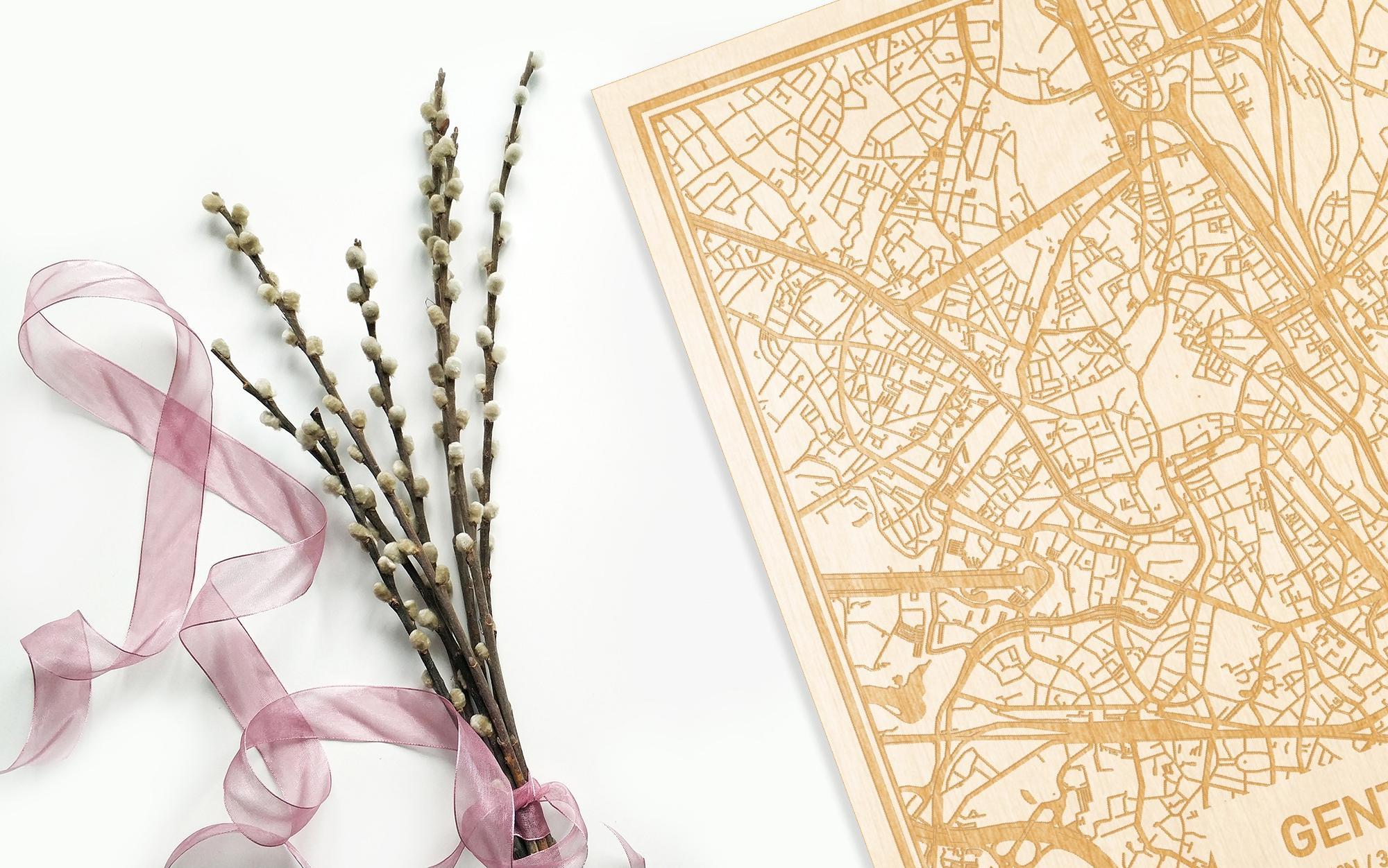 Hier ligt de houten plattegrond Gent naast een bloemetje als gepersonaliseerd cadeau voor haar.