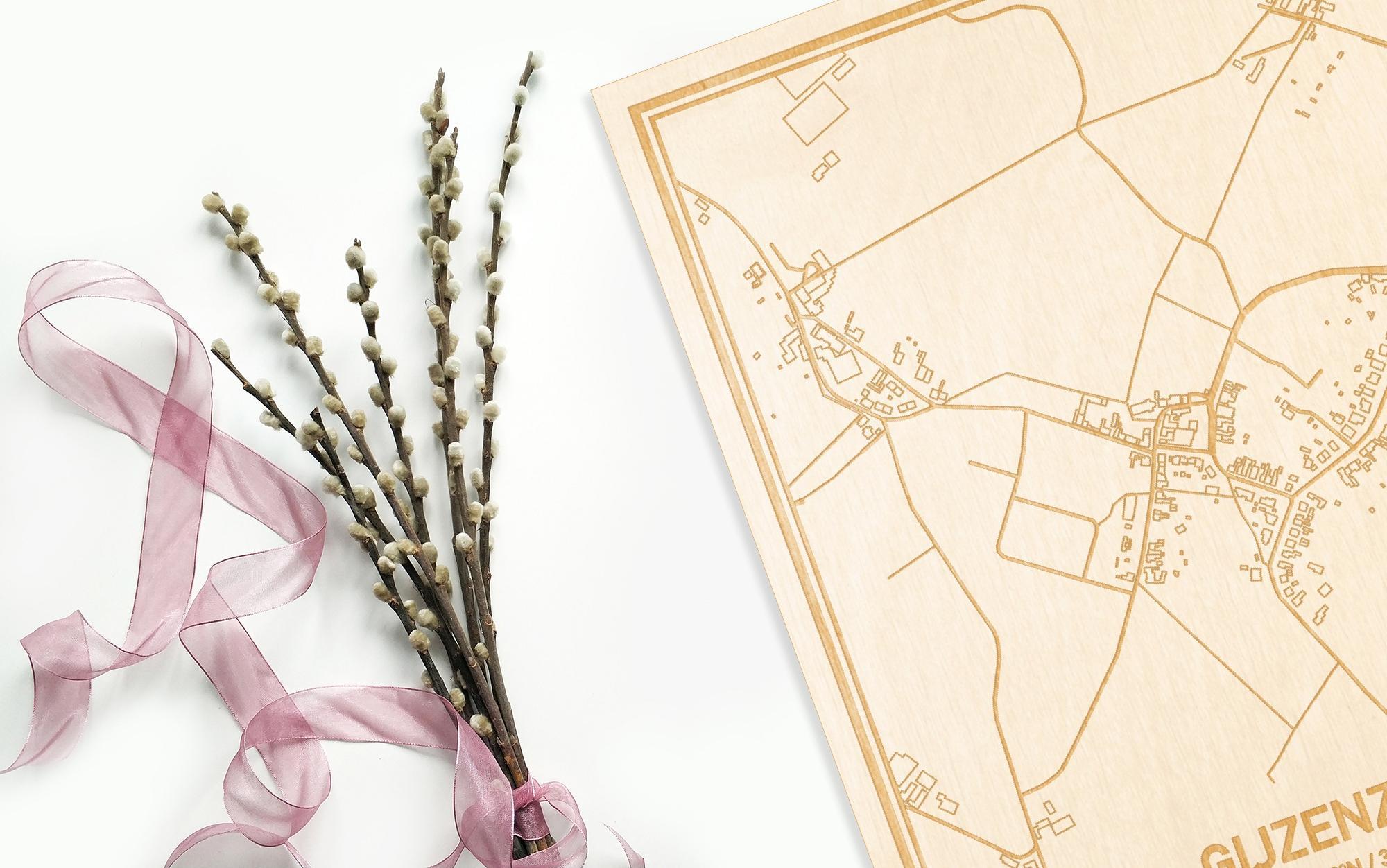 Hier ligt de houten plattegrond Gijzenzele naast een bloemetje als gepersonaliseerd cadeau voor haar.