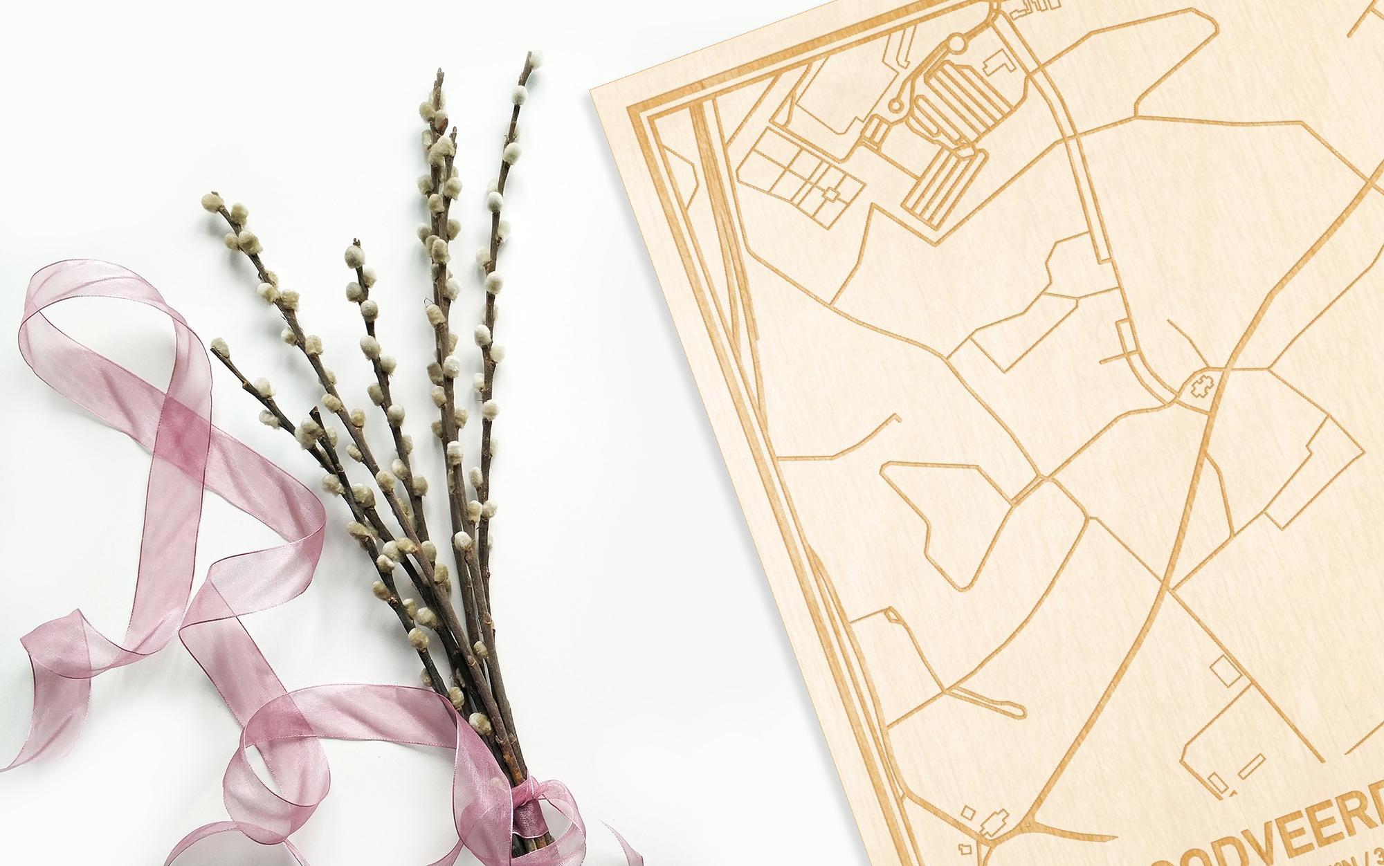 Hier ligt de houten plattegrond Godveerdegem naast een bloemetje als gepersonaliseerd cadeau voor haar.