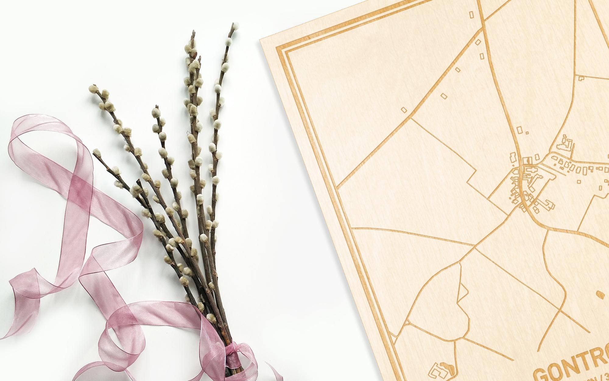Hier ligt de houten plattegrond Gontrode naast een bloemetje als gepersonaliseerd cadeau voor haar.