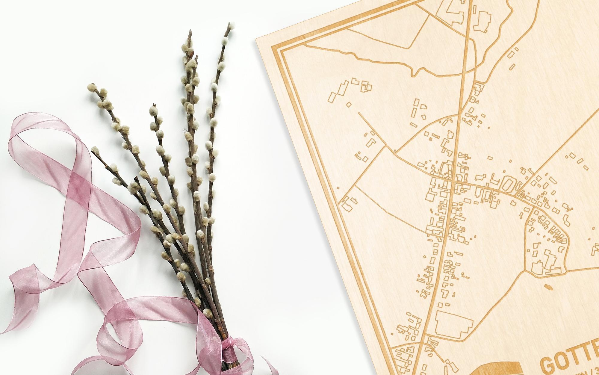 Hier ligt de houten plattegrond Gottem naast een bloemetje als gepersonaliseerd cadeau voor haar.