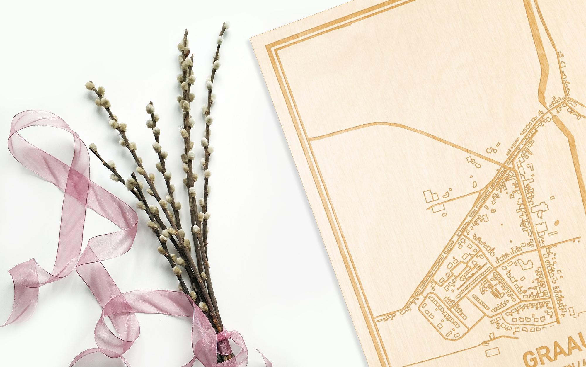 Hier ligt de houten plattegrond Graauw naast een bloemetje als gepersonaliseerd cadeau voor haar.