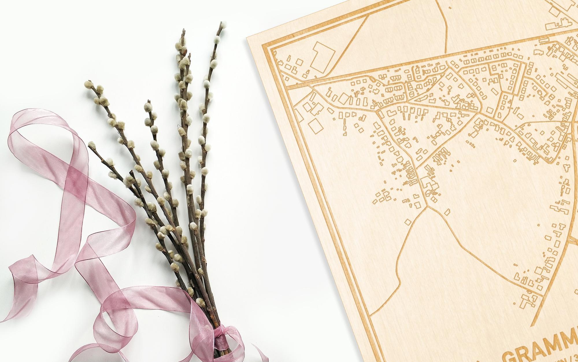 Hier ligt de houten plattegrond Grammene naast een bloemetje als gepersonaliseerd cadeau voor haar.
