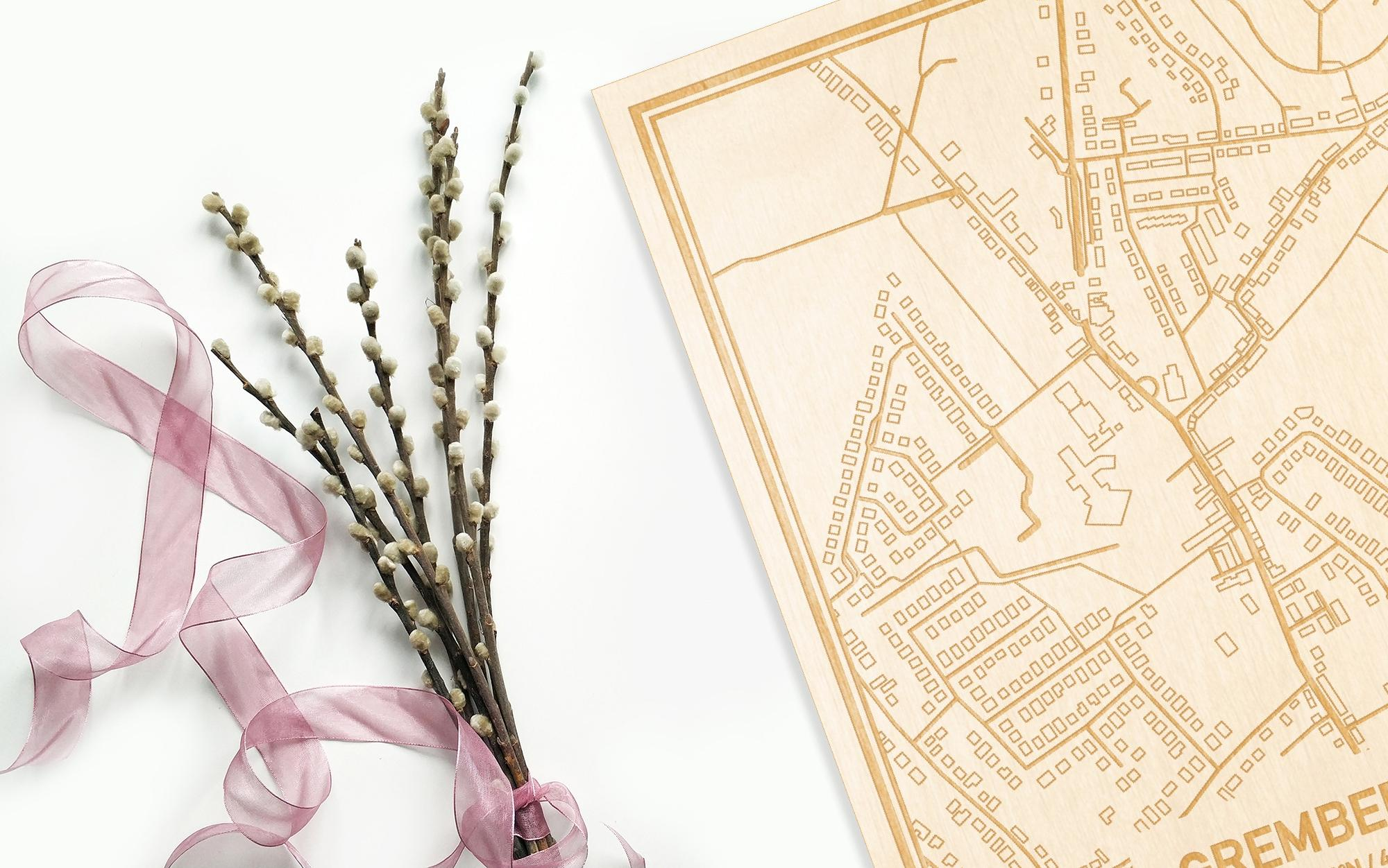 Hier ligt de houten plattegrond Grembergen naast een bloemetje als gepersonaliseerd cadeau voor haar.