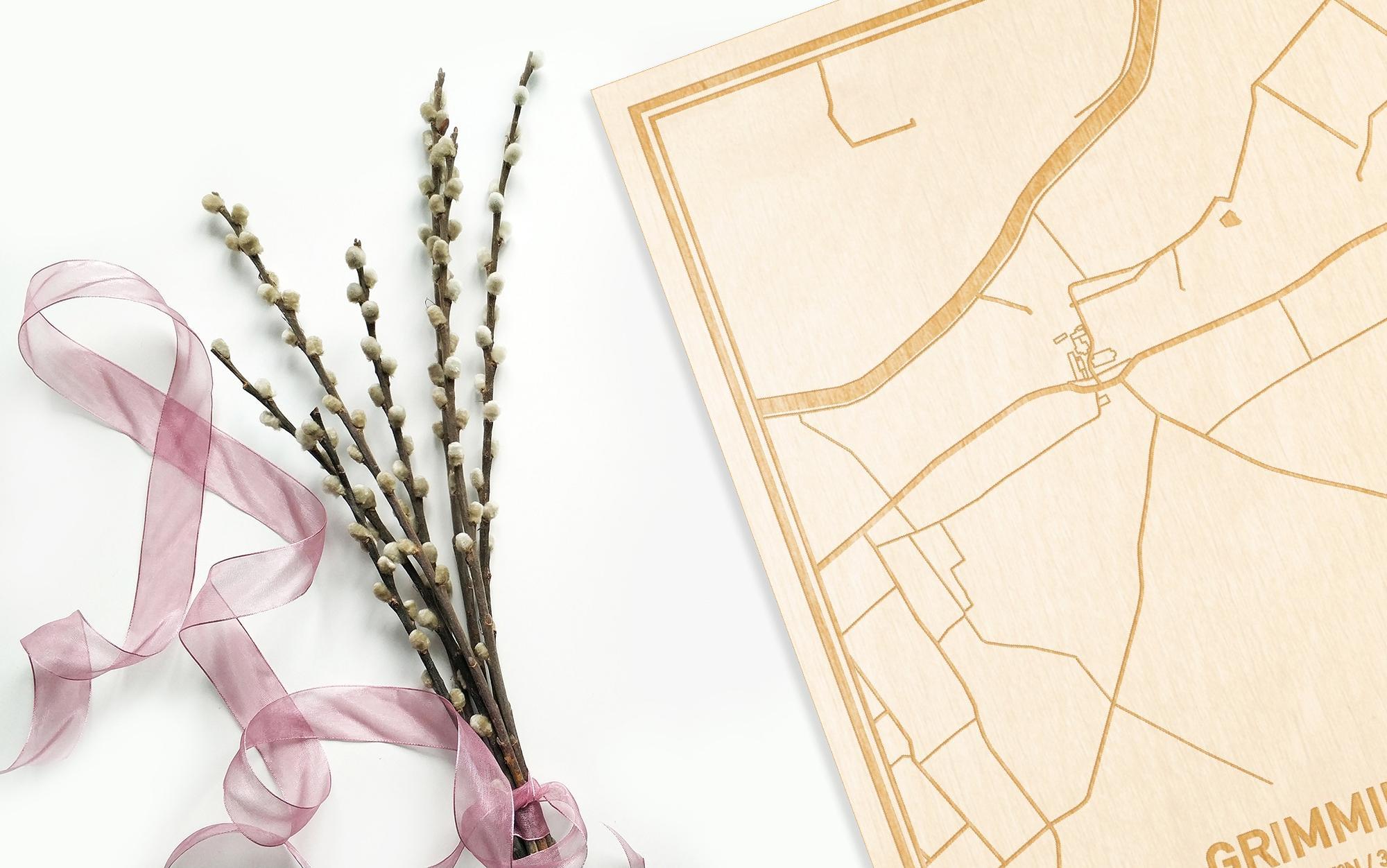 Hier ligt de houten plattegrond Grimminge naast een bloemetje als gepersonaliseerd cadeau voor haar.