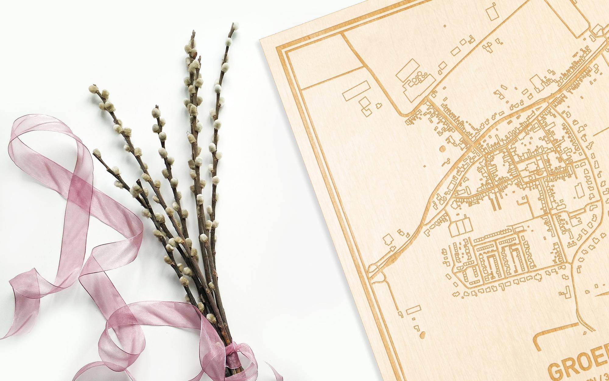 Hier ligt de houten plattegrond Groede naast een bloemetje als gepersonaliseerd cadeau voor haar.