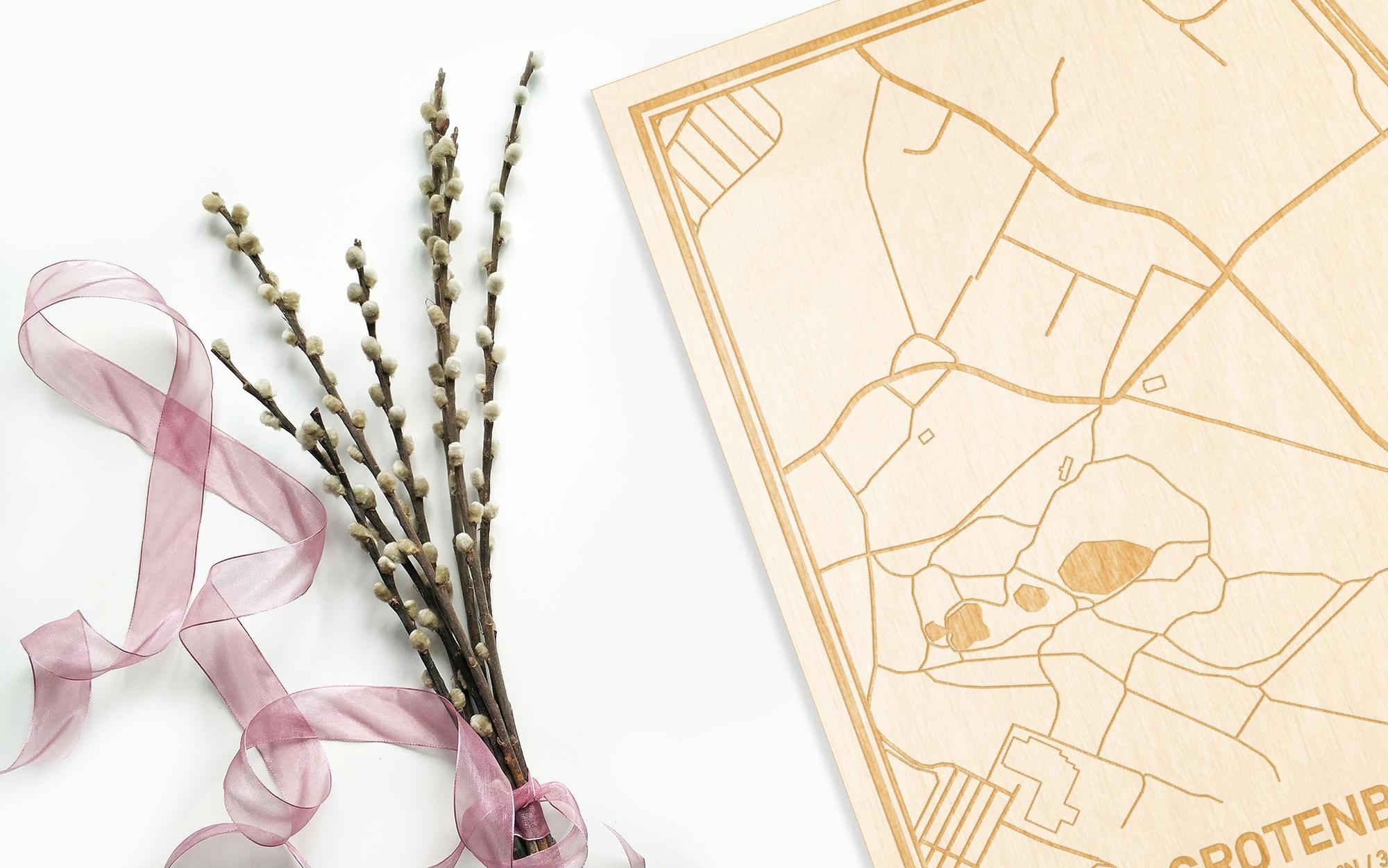 Hier ligt de houten plattegrond Grotenberge naast een bloemetje als gepersonaliseerd cadeau voor haar.