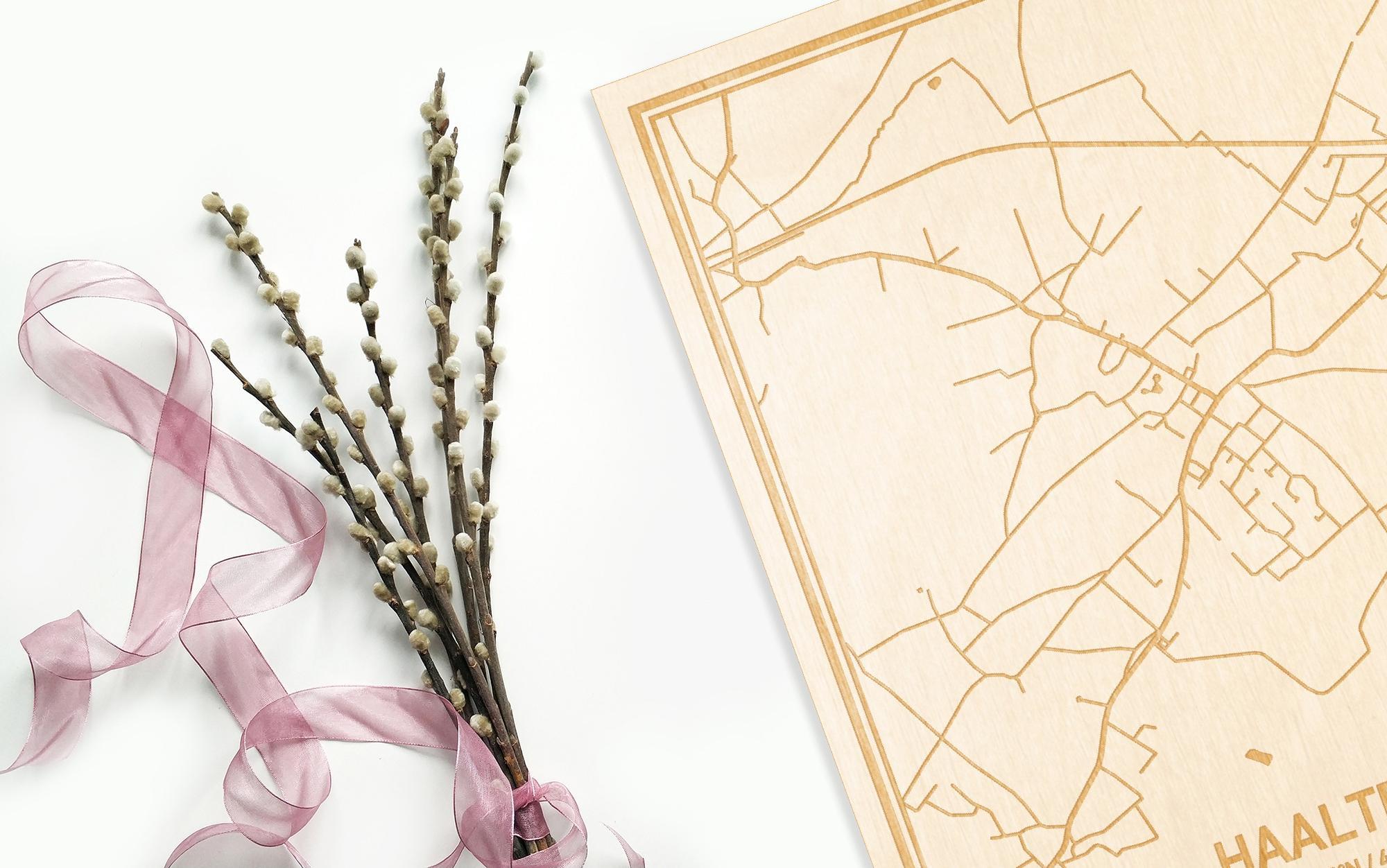 Hier ligt de houten plattegrond Haaltert naast een bloemetje als gepersonaliseerd cadeau voor haar.