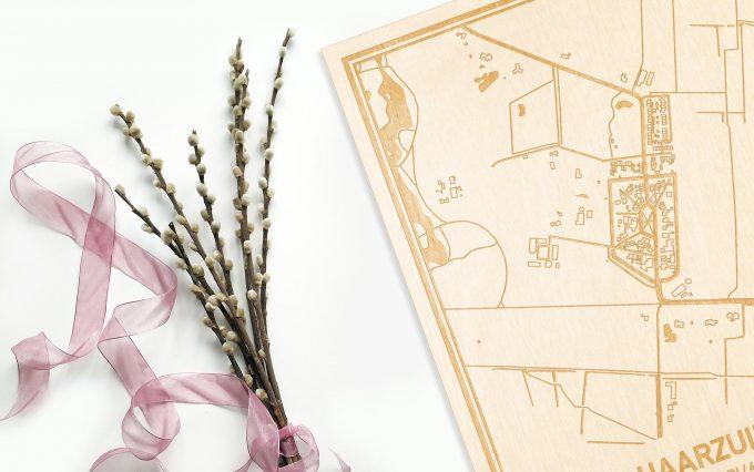 Hier ligt de houten plattegrond Haarzuilens naast een bloemetje als gepersonaliseerd cadeau voor haar.