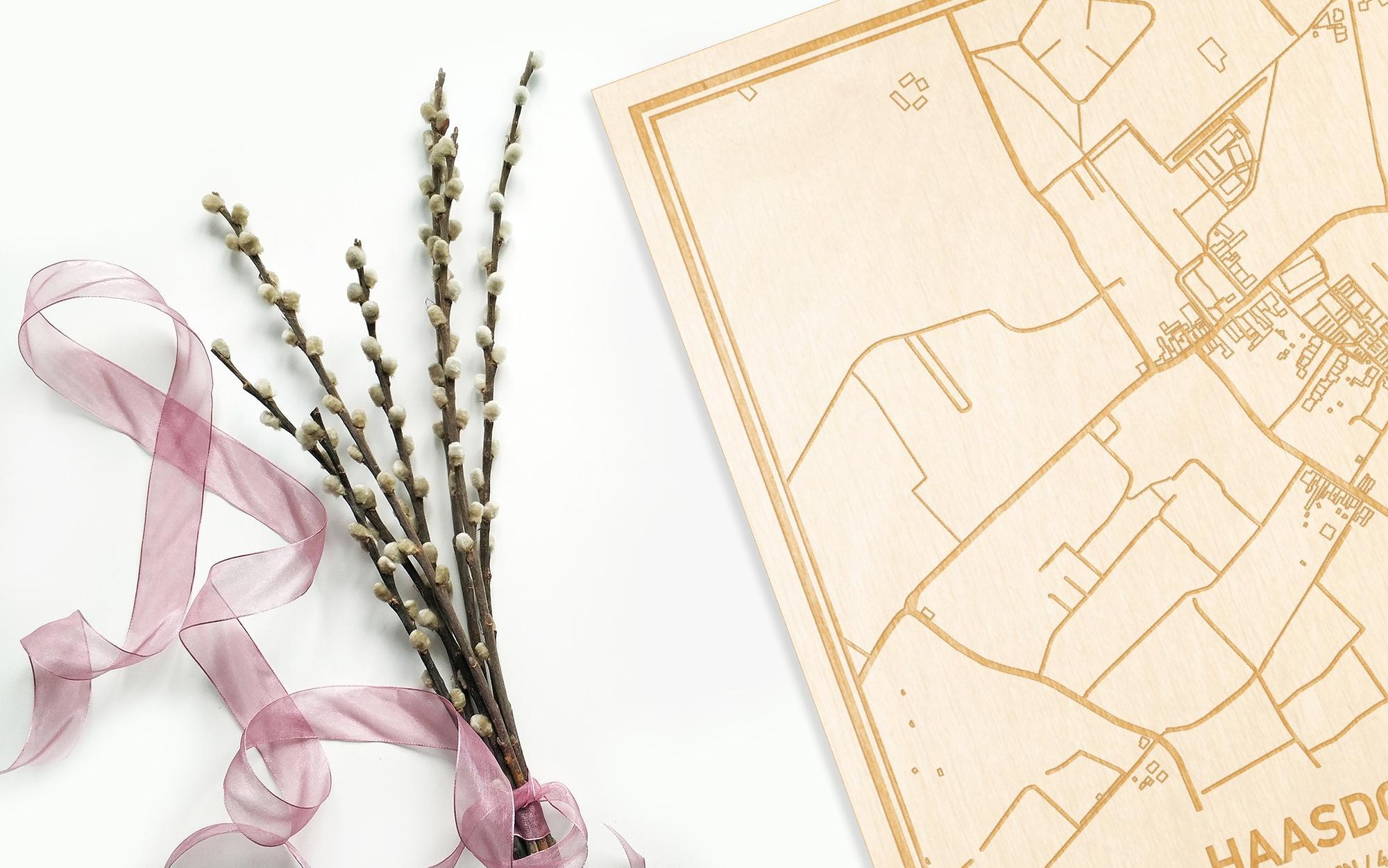 Hier ligt de houten plattegrond Haasdonk naast een bloemetje als gepersonaliseerd cadeau voor haar.