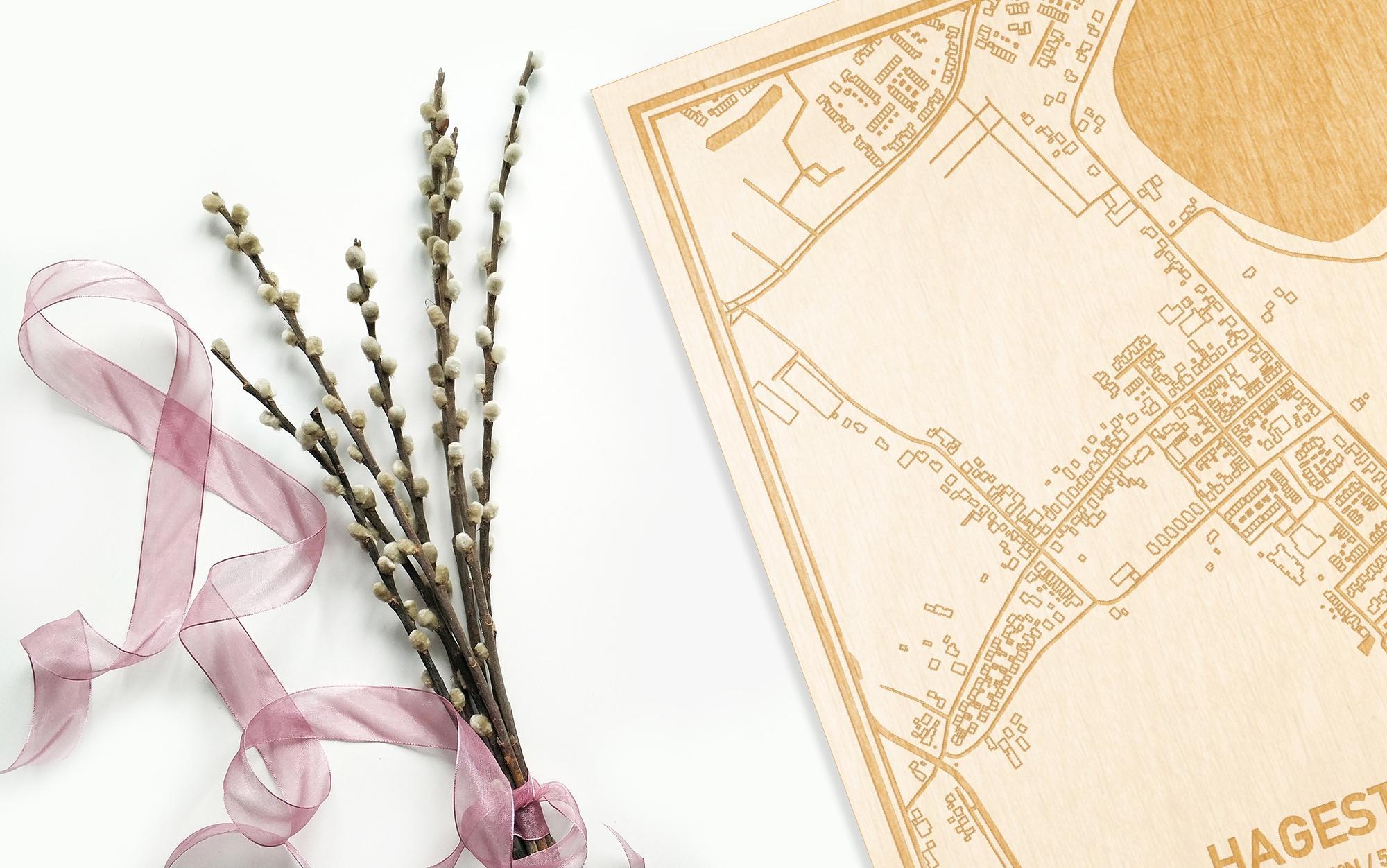 Hier ligt de houten plattegrond Hagestein naast een bloemetje als gepersonaliseerd cadeau voor haar.