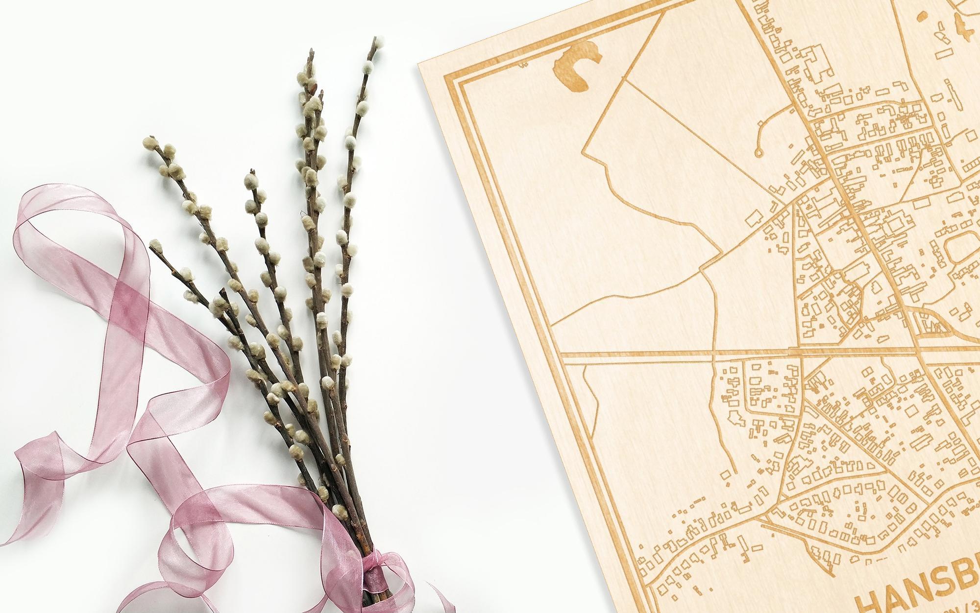 Hier ligt de houten plattegrond Hansbeke naast een bloemetje als gepersonaliseerd cadeau voor haar.