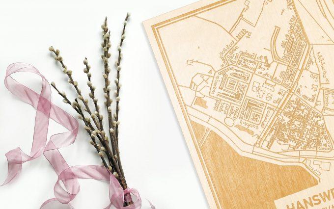 Hier ligt de houten plattegrond Hansweert naast een bloemetje als gepersonaliseerd cadeau voor haar.