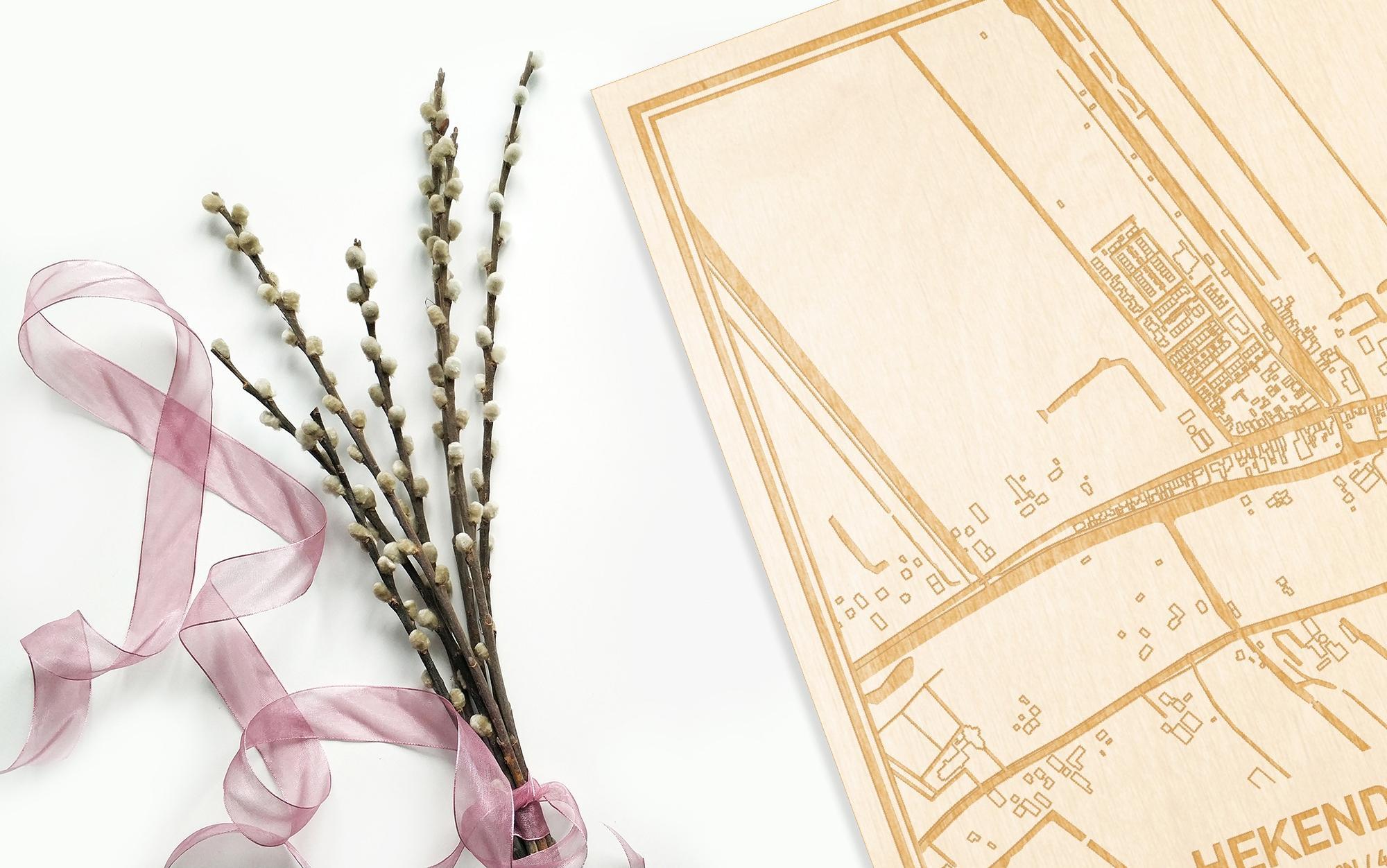 Hier ligt de houten plattegrond Hekendorp naast een bloemetje als gepersonaliseerd cadeau voor haar.
