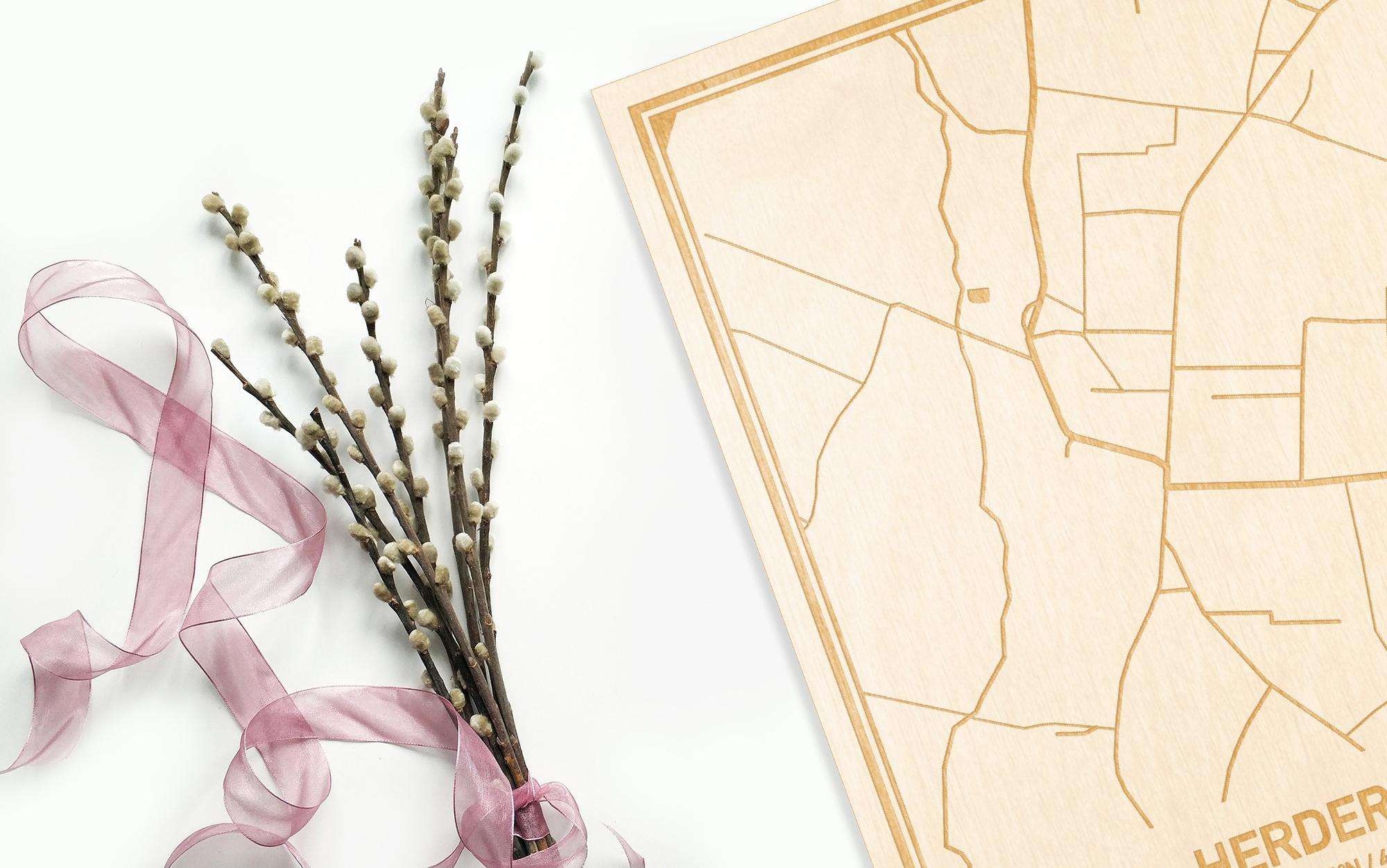 Hier ligt de houten plattegrond Herdersem naast een bloemetje als gepersonaliseerd cadeau voor haar.