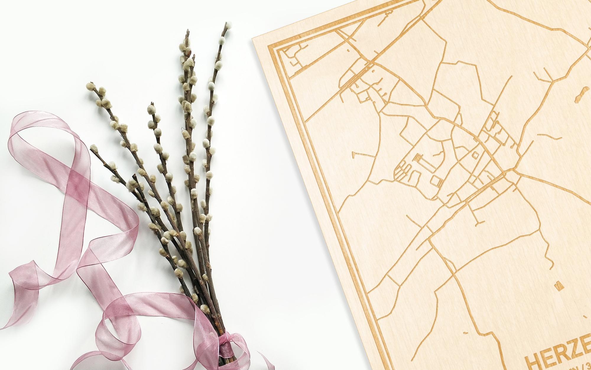 Hier ligt de houten plattegrond Herzele naast een bloemetje als gepersonaliseerd cadeau voor haar.
