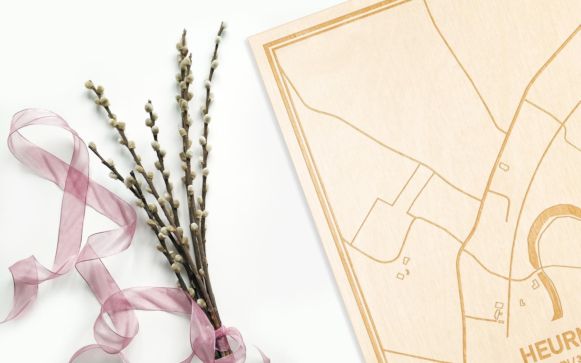 Hier ligt de houten plattegrond Heurne naast een bloemetje als gepersonaliseerd cadeau voor haar.