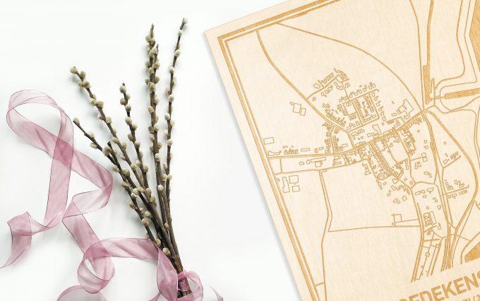 Hier ligt de houten plattegrond Hoedekenskerke naast een bloemetje als gepersonaliseerd cadeau voor haar.