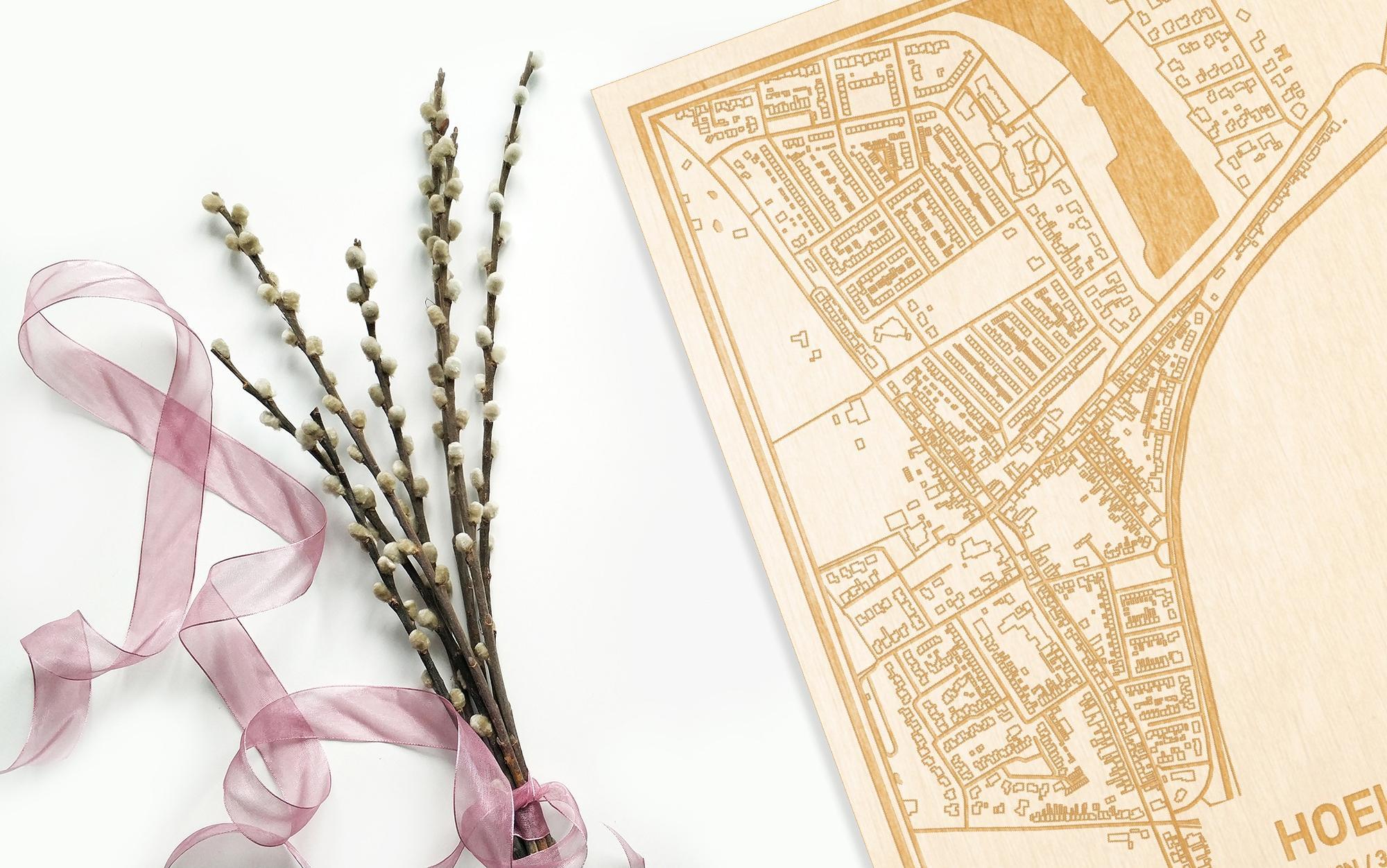 Hier ligt de houten plattegrond Hoek naast een bloemetje als gepersonaliseerd cadeau voor haar.