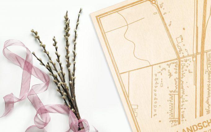 Hier ligt de houten plattegrond Hollandsche Rading naast een bloemetje als gepersonaliseerd cadeau voor haar.
