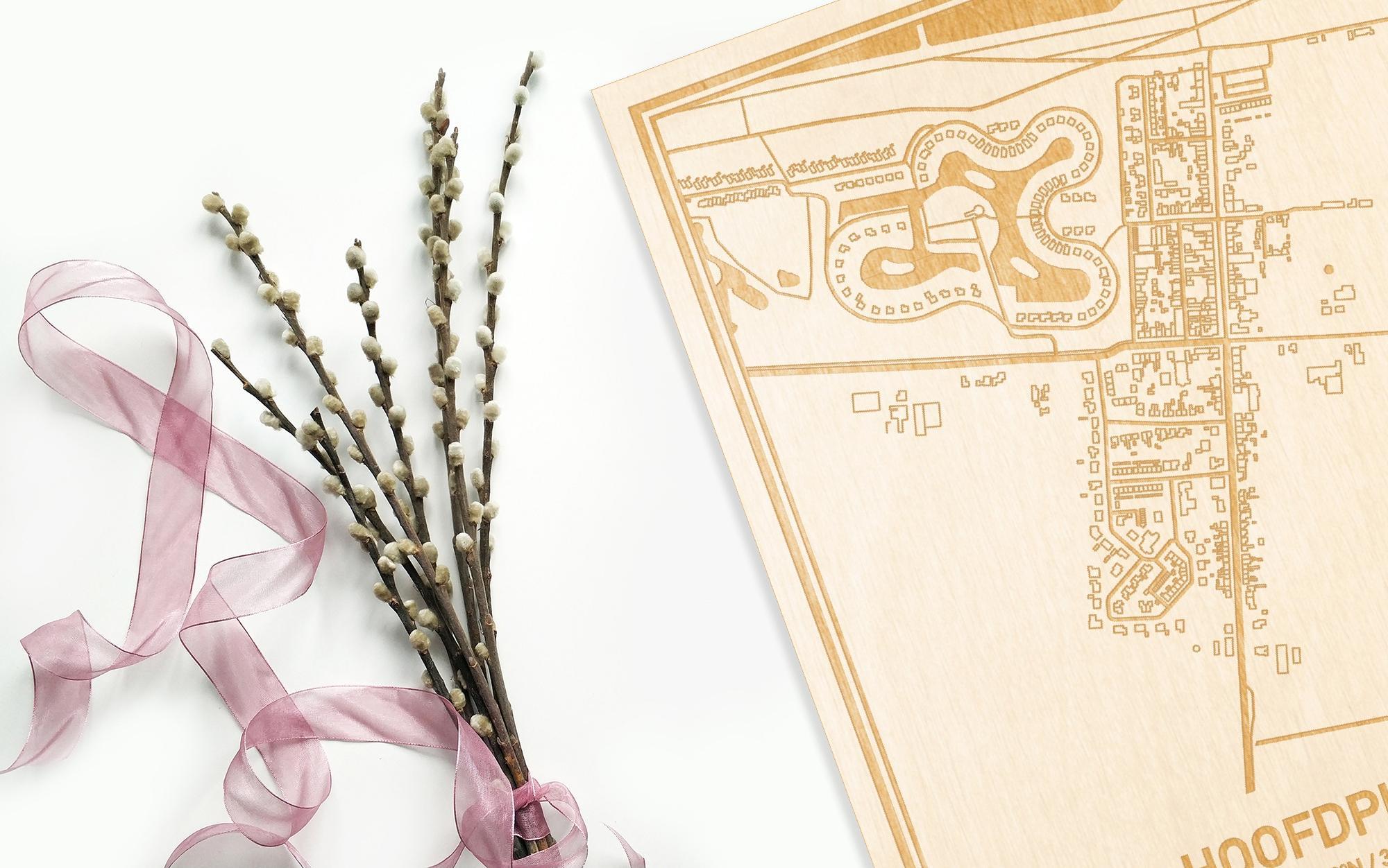 Hier ligt de houten plattegrond Hoofdplaat naast een bloemetje als gepersonaliseerd cadeau voor haar.