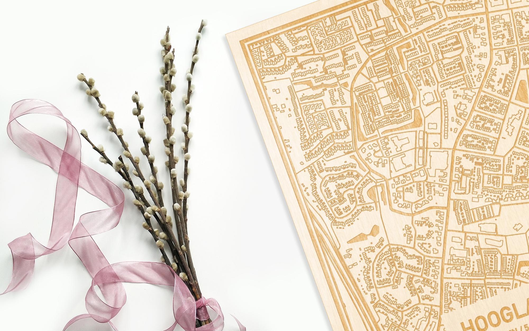 Hier ligt de houten plattegrond Hoogland naast een bloemetje als gepersonaliseerd cadeau voor haar.