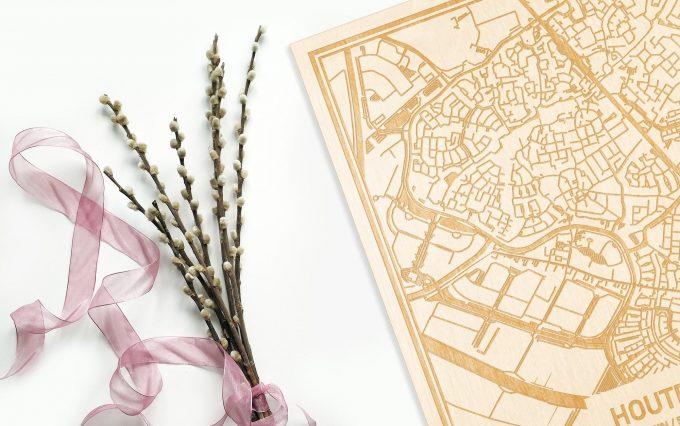 Hier ligt de houten plattegrond Houten naast een bloemetje als gepersonaliseerd cadeau voor haar.