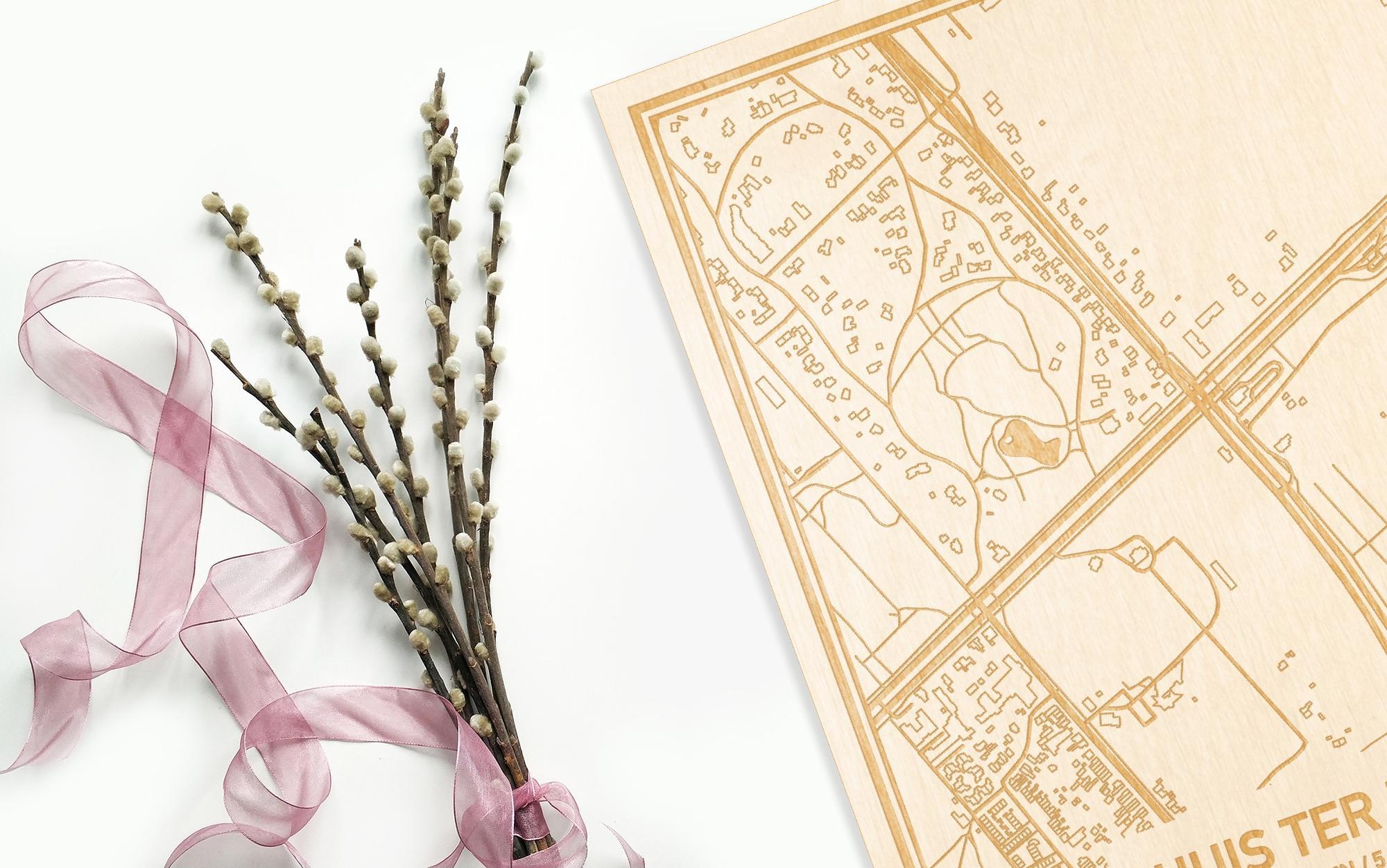 Hier ligt de houten plattegrond Huis ter Heide naast een bloemetje als gepersonaliseerd cadeau voor haar.