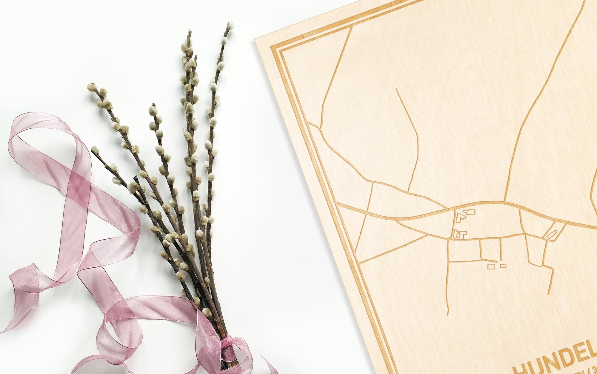 Hier ligt de houten plattegrond Hundelgem naast een bloemetje als gepersonaliseerd cadeau voor haar.