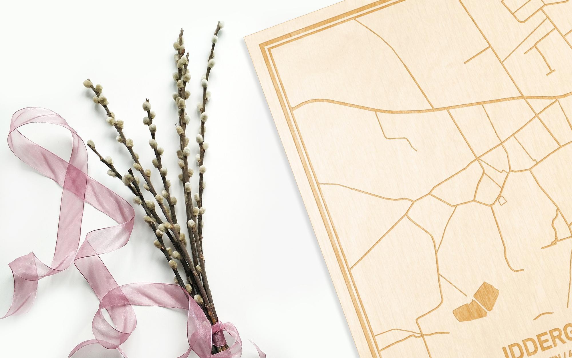 Hier ligt de houten plattegrond Iddergem naast een bloemetje als gepersonaliseerd cadeau voor haar.