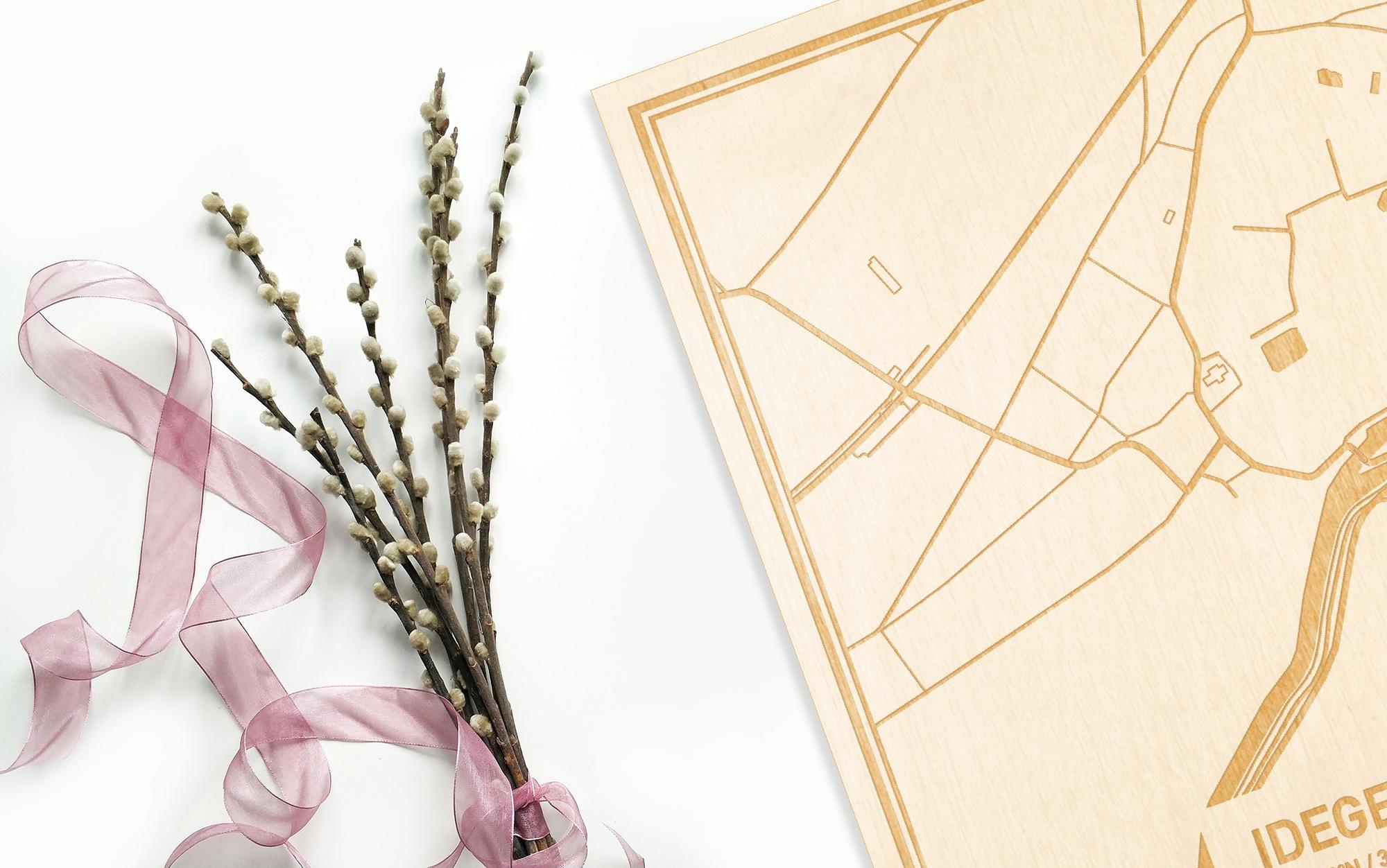 Hier ligt de houten plattegrond Idegem naast een bloemetje als gepersonaliseerd cadeau voor haar.