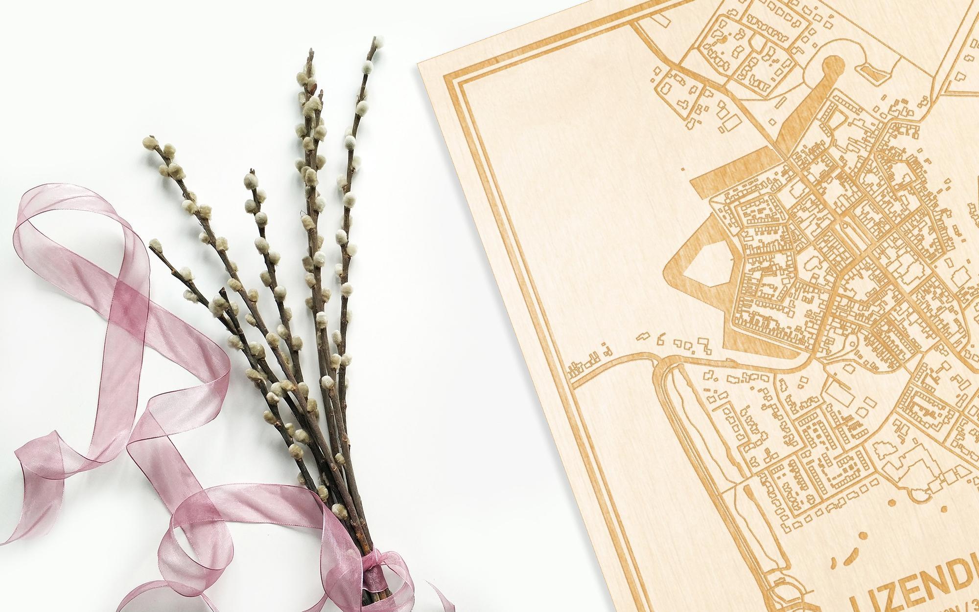 Hier ligt de houten plattegrond IJzendijke naast een bloemetje als gepersonaliseerd cadeau voor haar.