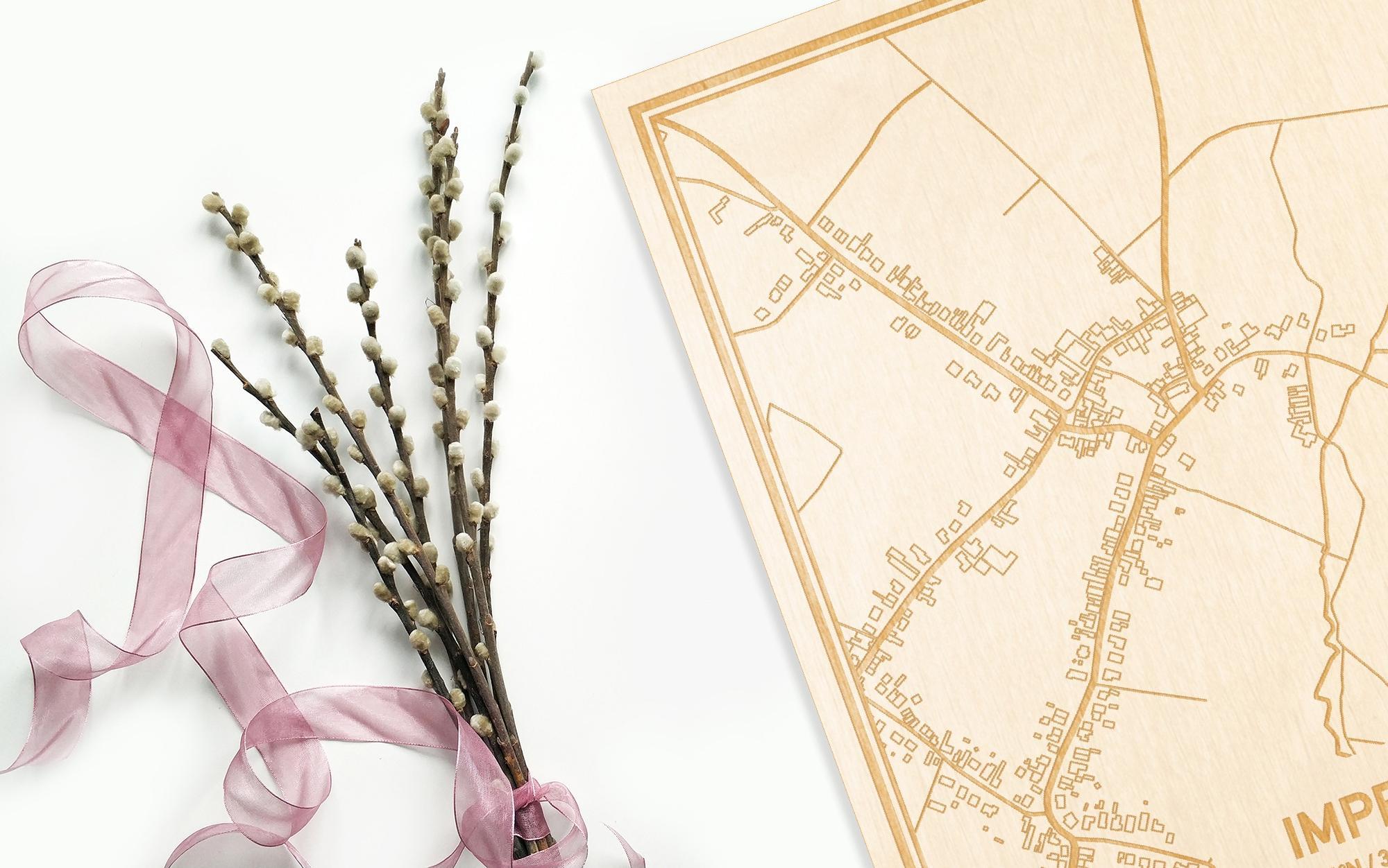 Hier ligt de houten plattegrond Impe naast een bloemetje als gepersonaliseerd cadeau voor haar.
