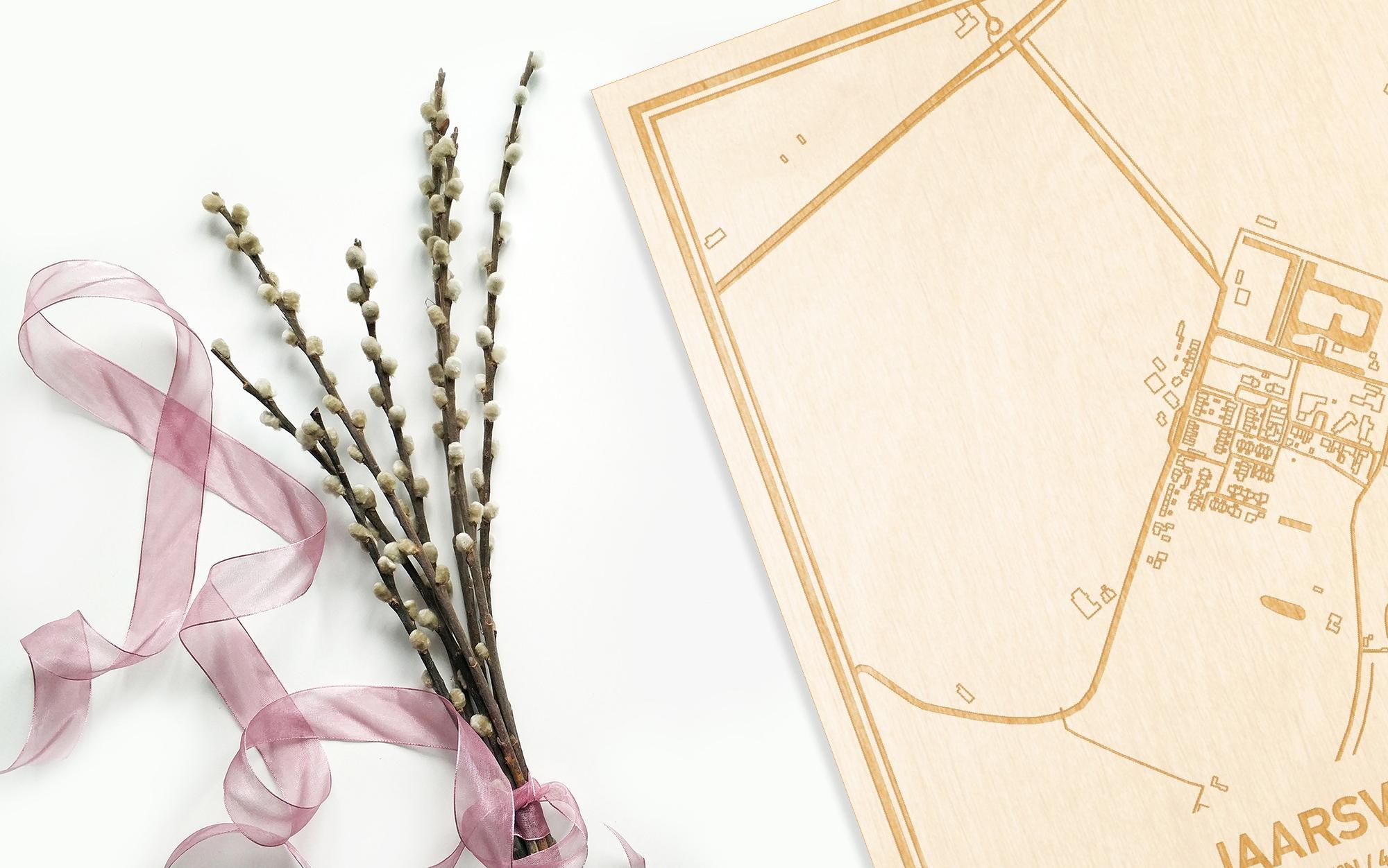 Hier ligt de houten plattegrond Jaarsveld naast een bloemetje als gepersonaliseerd cadeau voor haar.