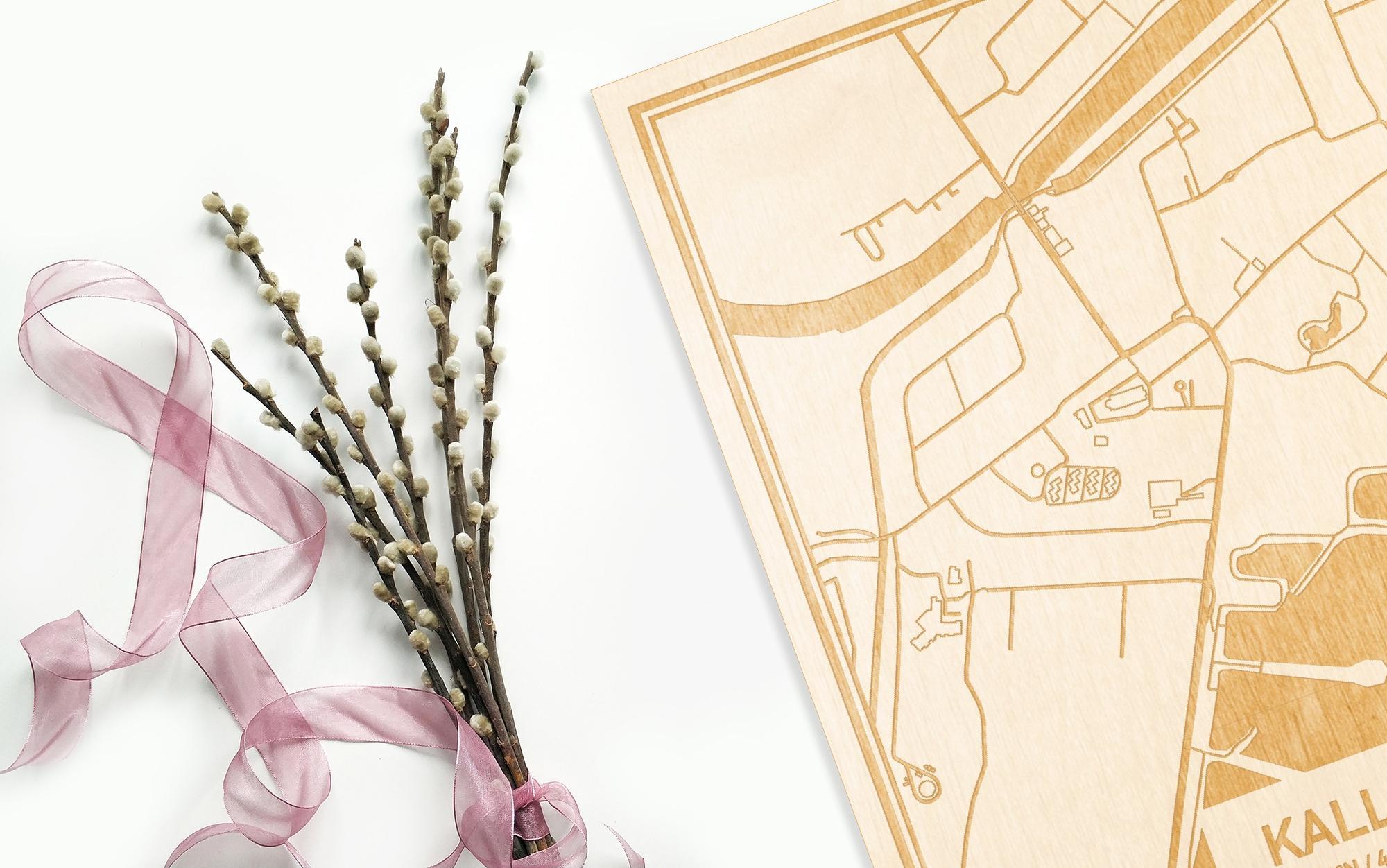 Hier ligt de houten plattegrond Kallo naast een bloemetje als gepersonaliseerd cadeau voor haar.