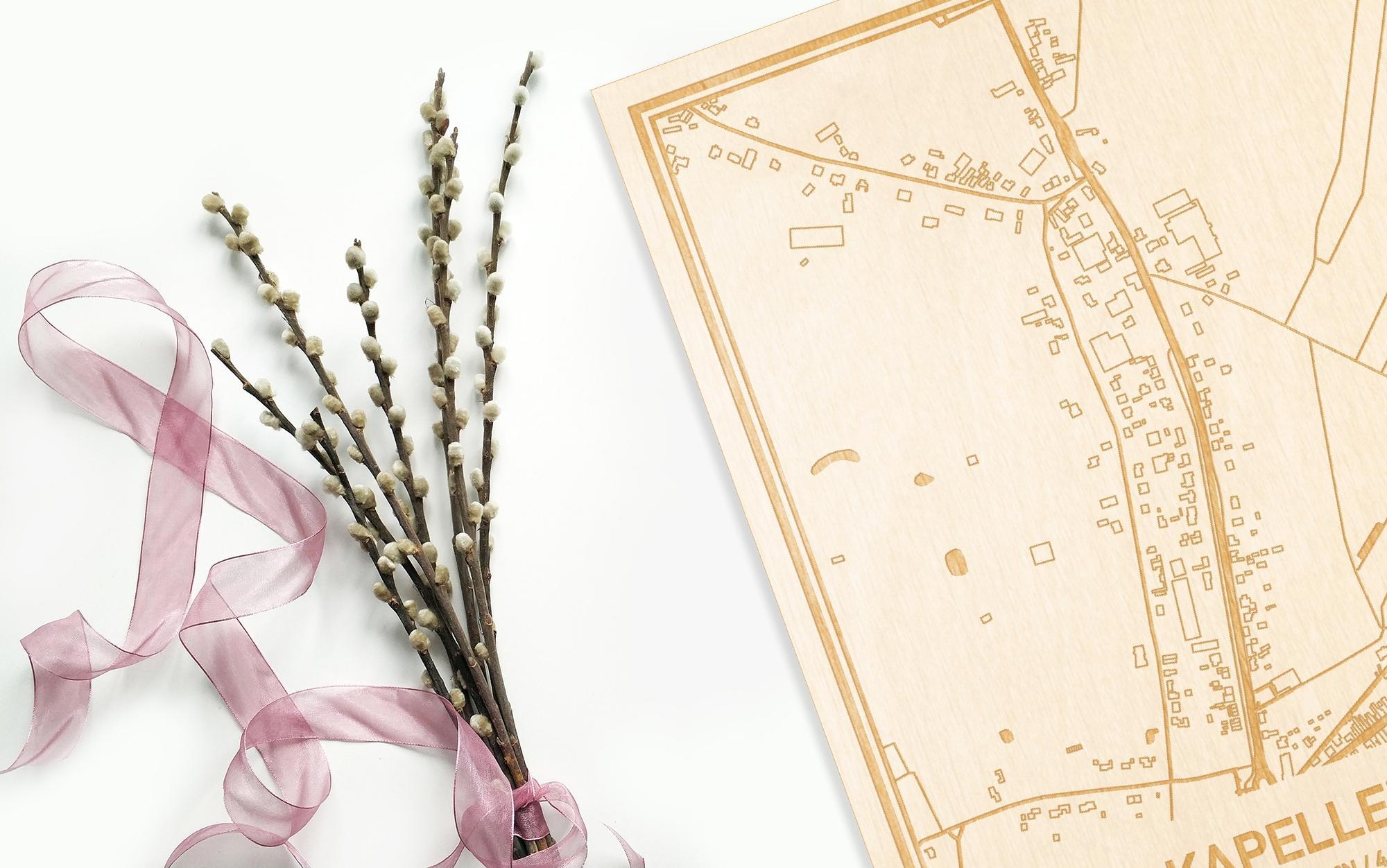 Hier ligt de houten plattegrond Kapellebrug naast een bloemetje als gepersonaliseerd cadeau voor haar.
